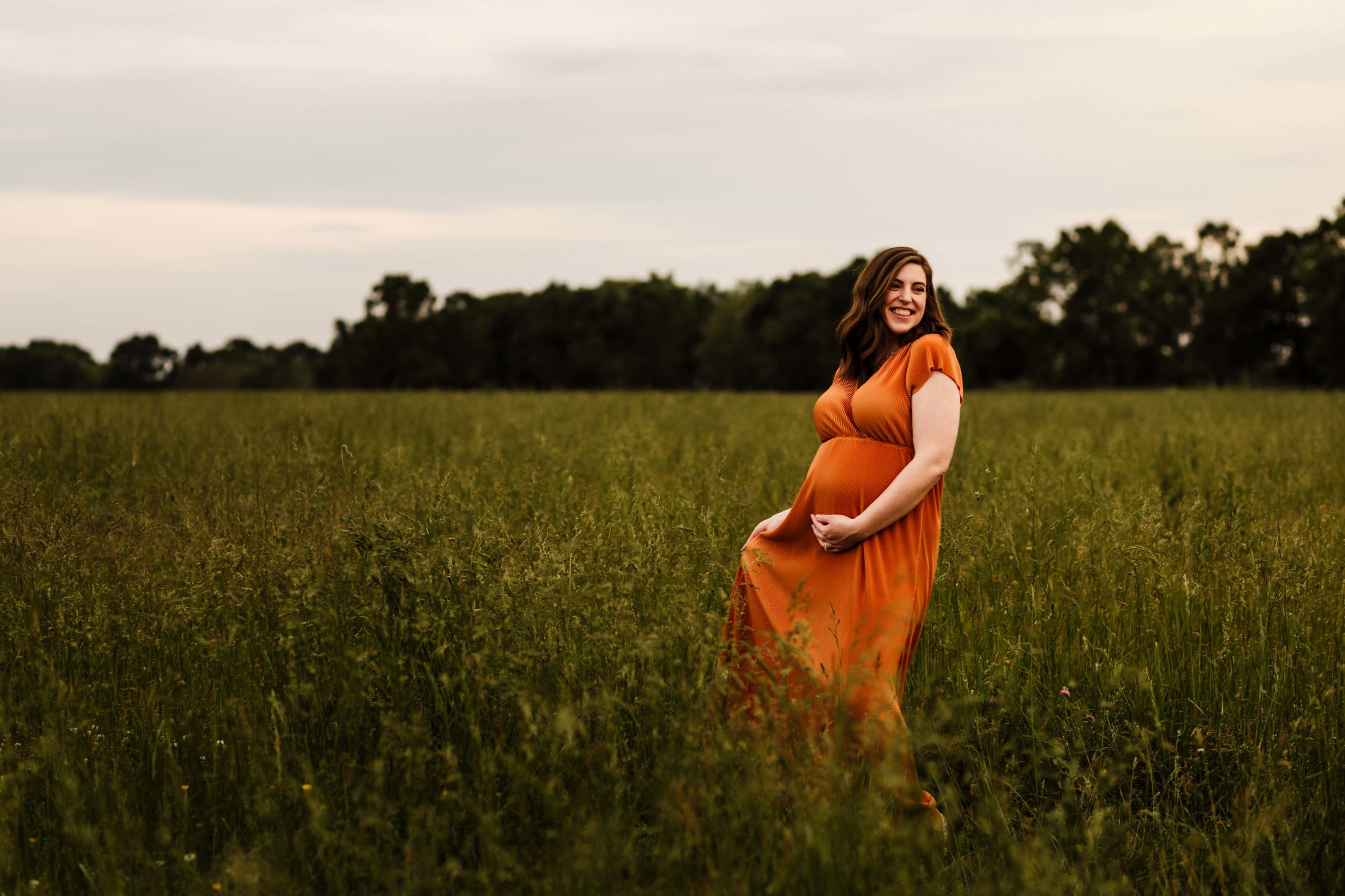 Pregnant woman standing in a tall grass field in a rust colored dress.