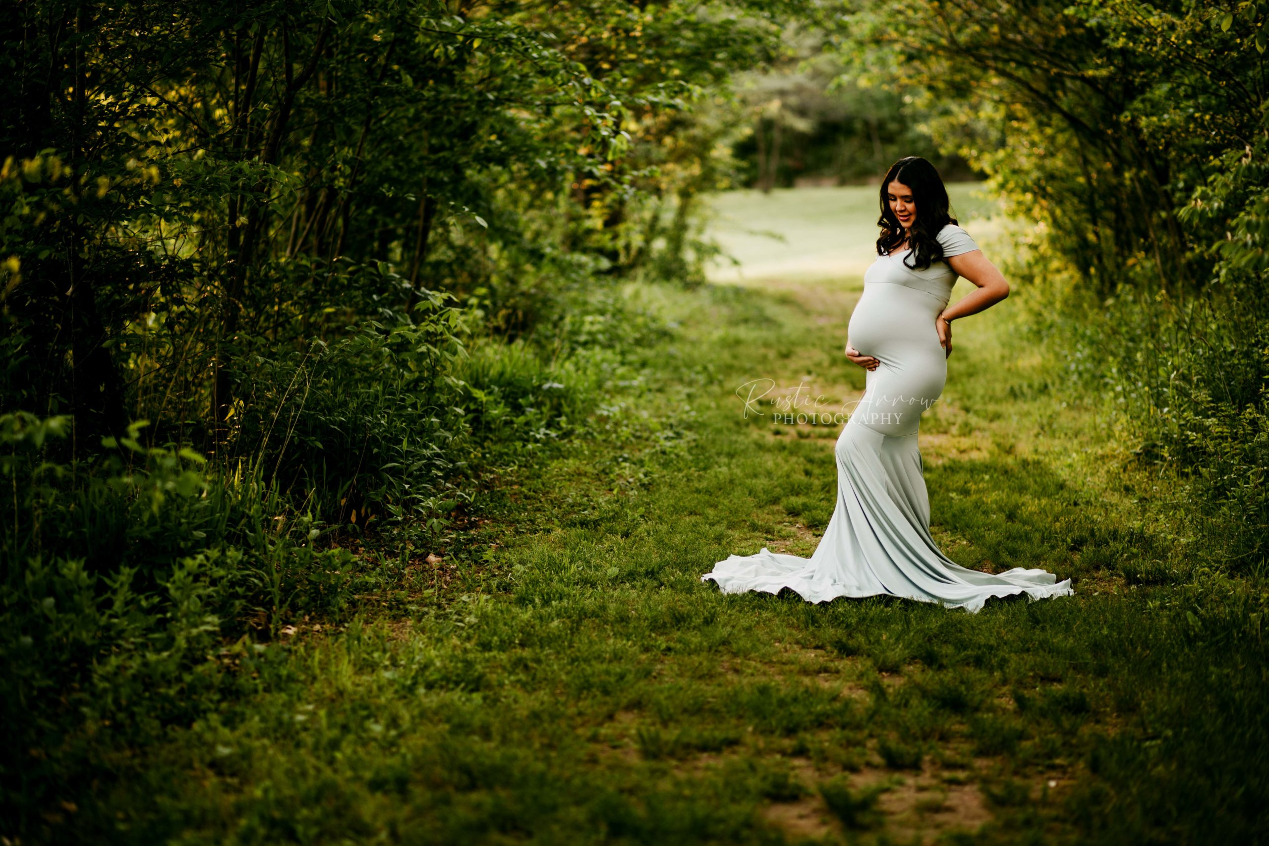 Pregnant woman cradling her belly under trees on a trail in Cave Springs