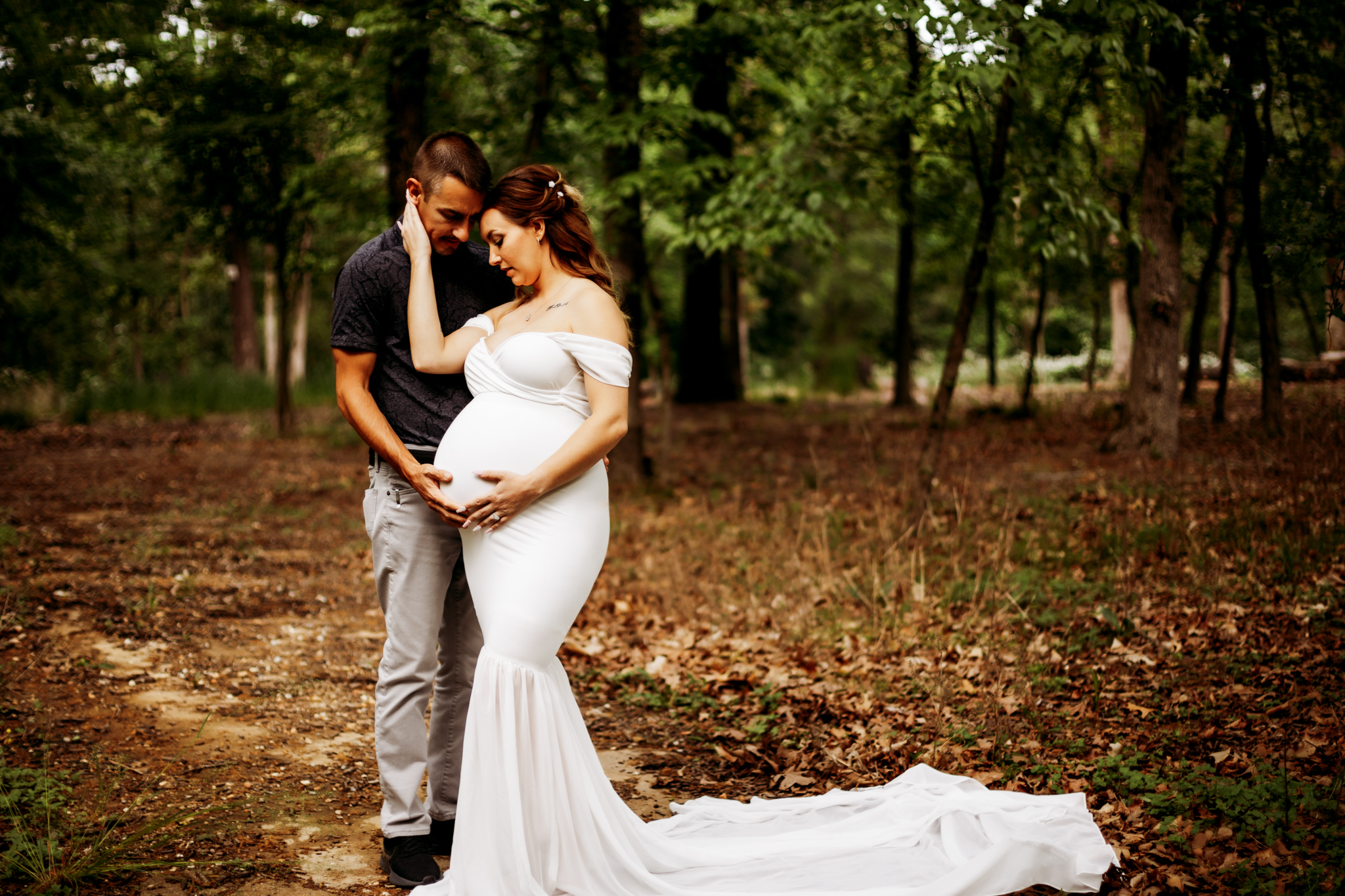 pregnant woman in white gown holding husbands face looking down at baby bump