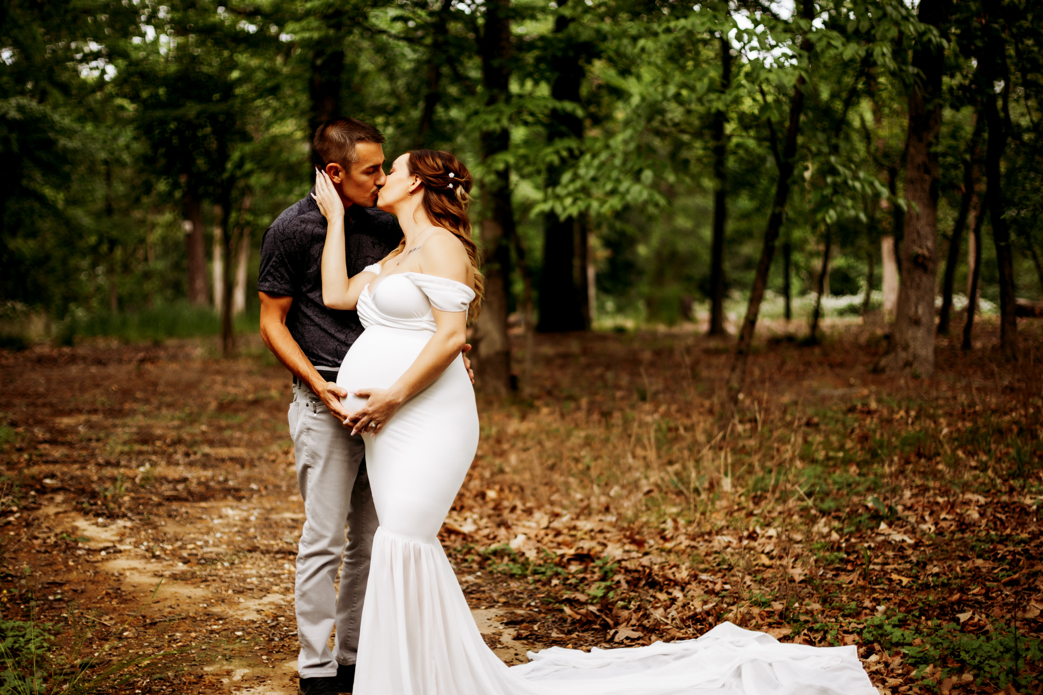 pregnant woman kissing her husband while cradling her baby during her Crystal Bridges maternity photography session
