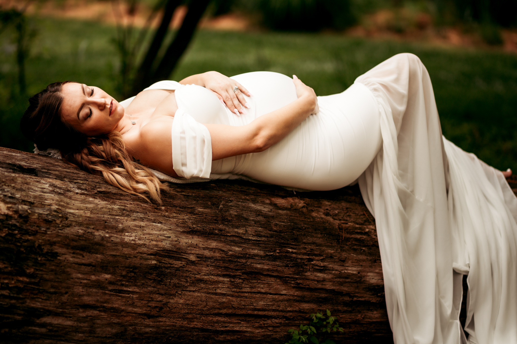 pregnant woman laying on log while wearing white gown and cradling belly