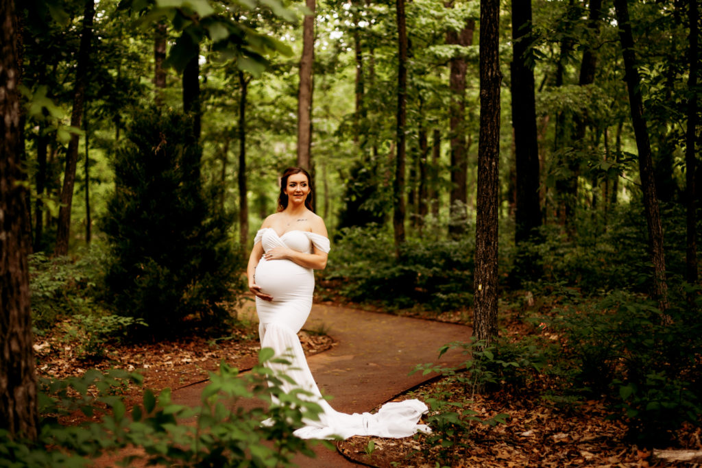 pregnant woman in white dress cradling her baby bump in a wooded area