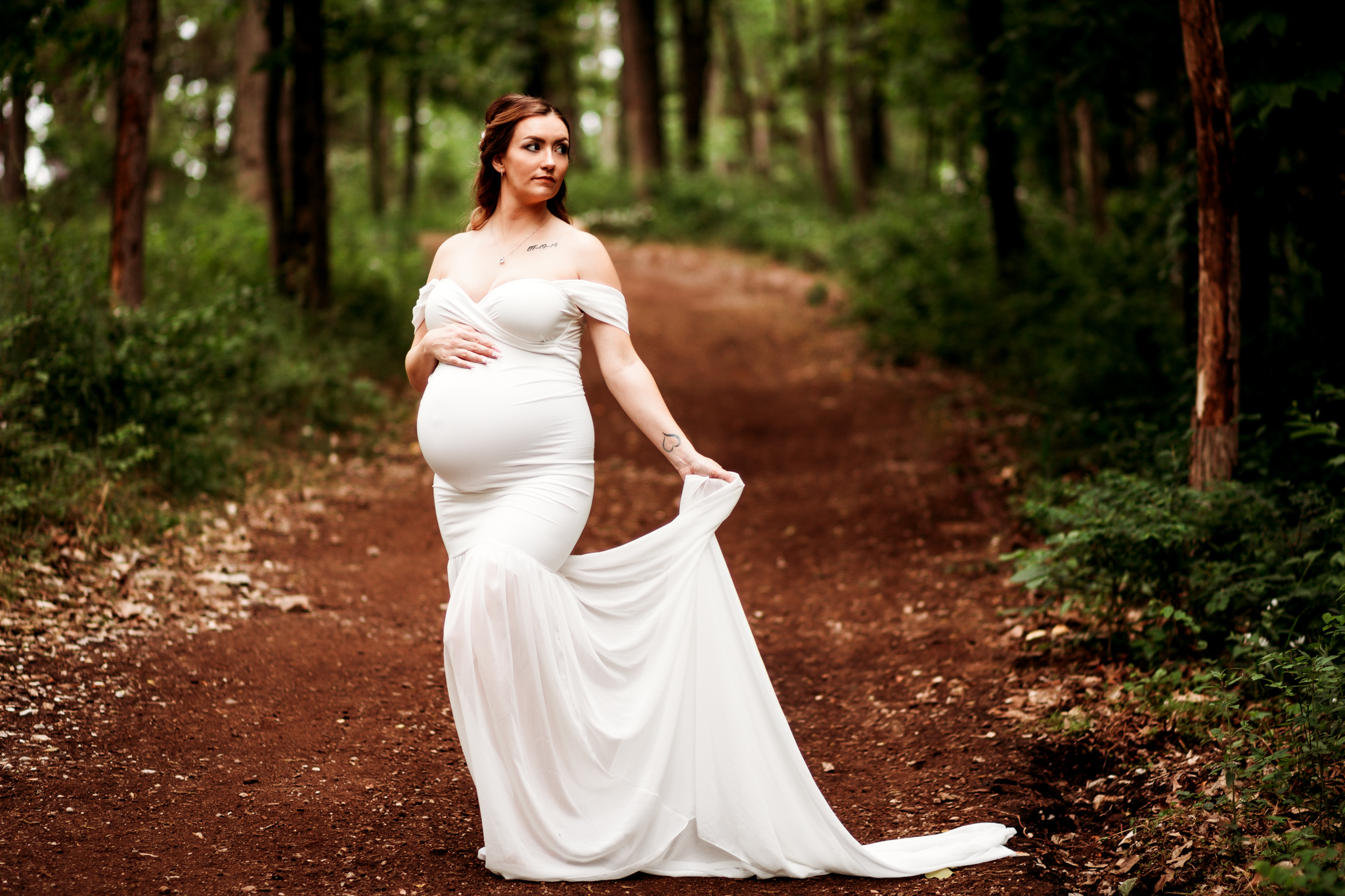 pregnant woman in white gown in woods and holding train of gown