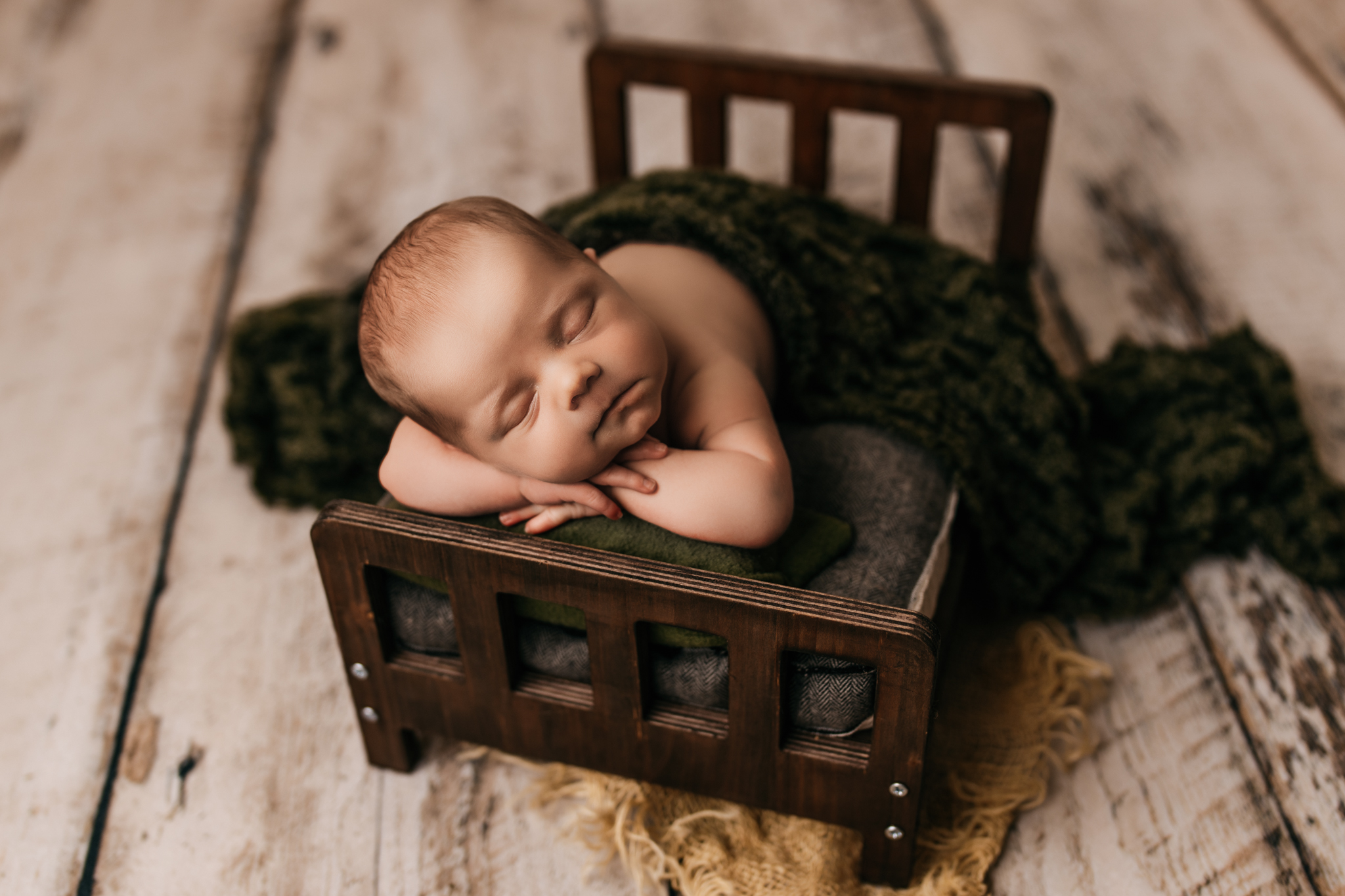 Baby laying on baby bed with hands under its head