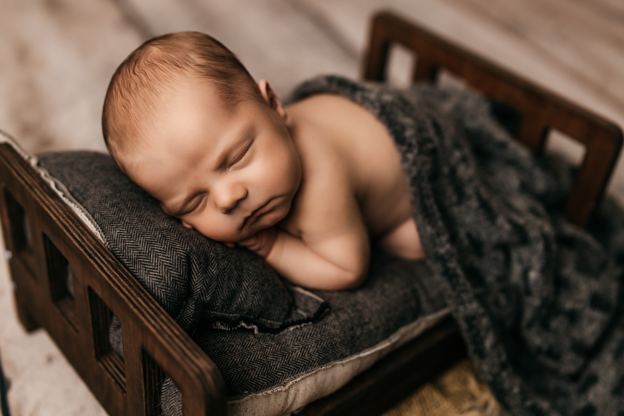 Baby laying on baby bed curled up with head on pillow
