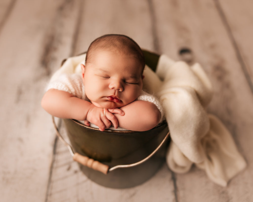 baby with head on hands inside bucket on white wood for newborn photography session