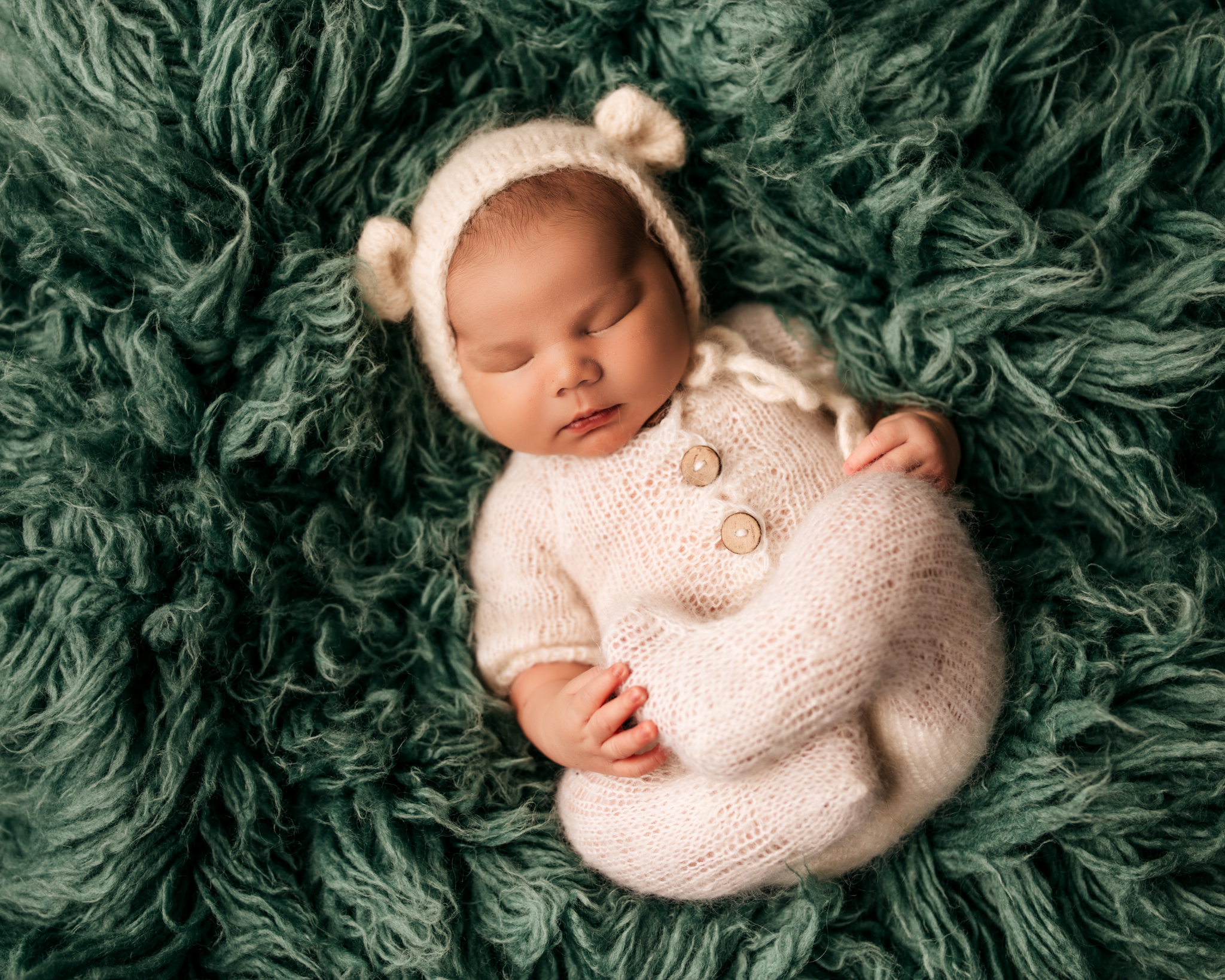 Baby in knit outfit with bear ear bonnet on a green shag carpet