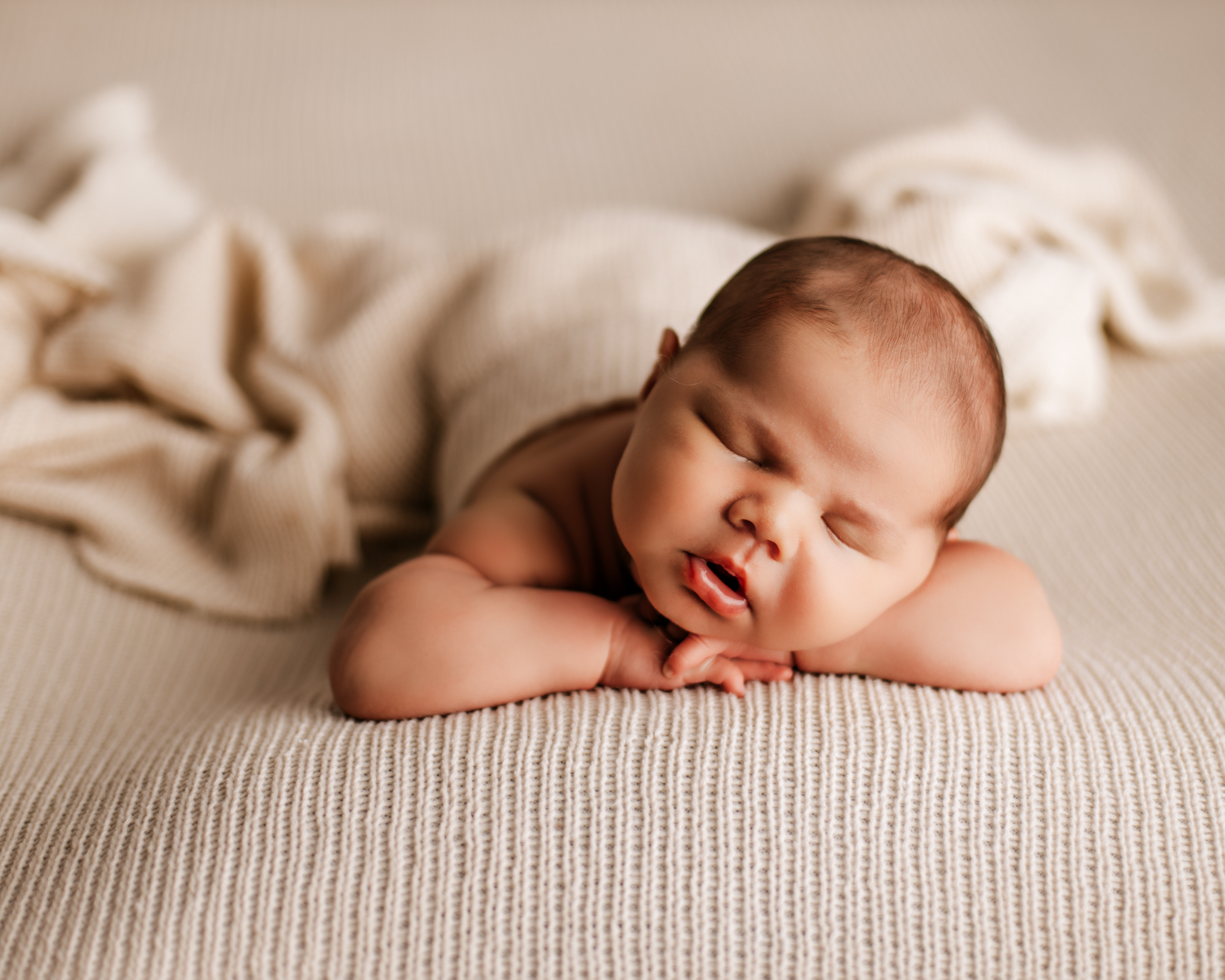 baby laying on cream backdrop with head on hands sleeping