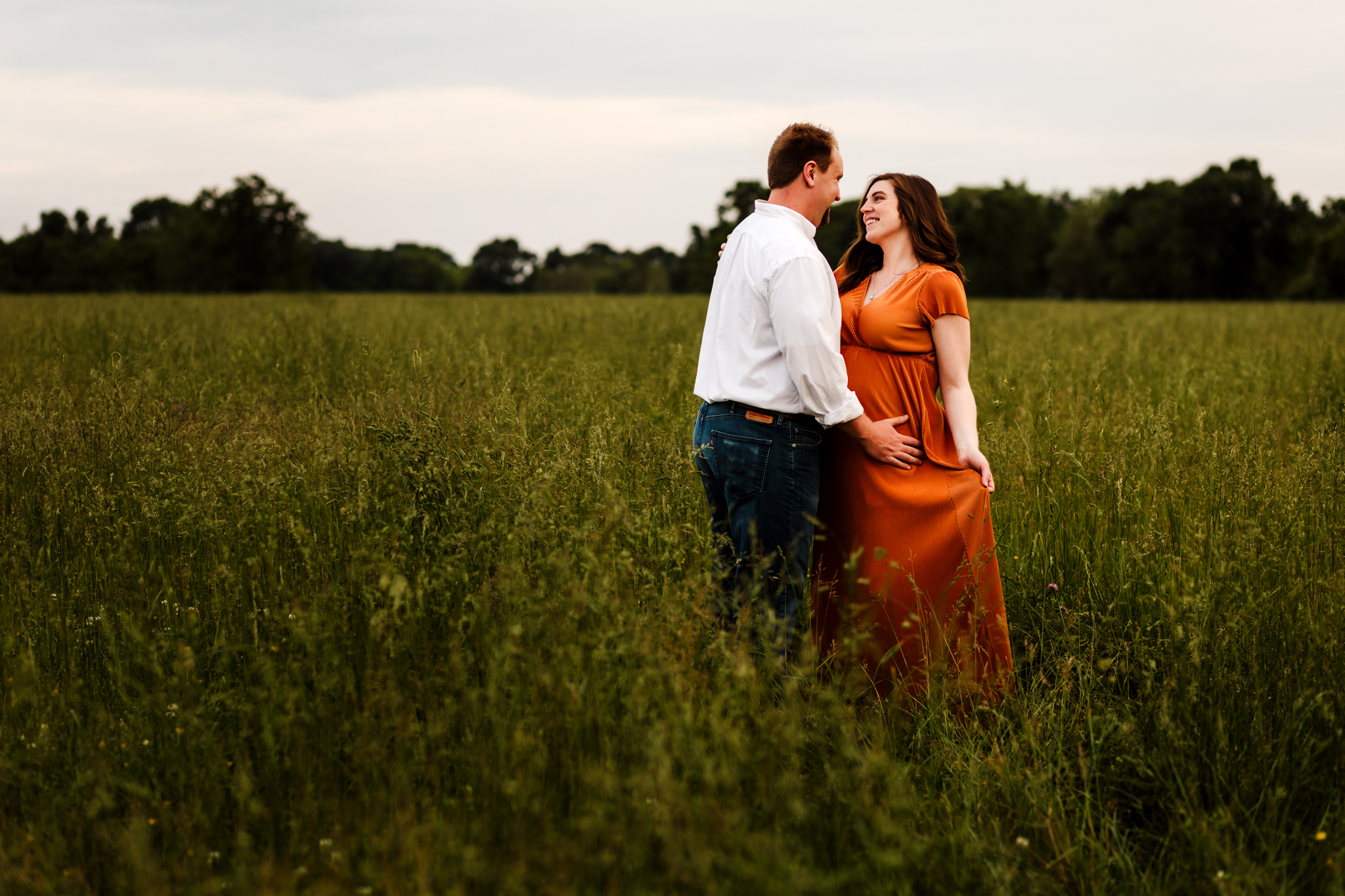 pregnant woman looking at her husband while holding maternity gown in overgrown field