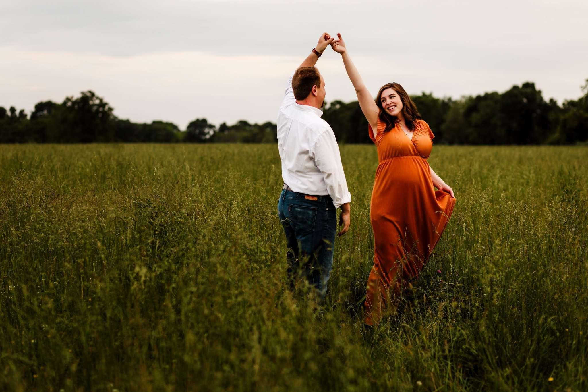 pregnant women dancing in orange dress with husband in overgrown field