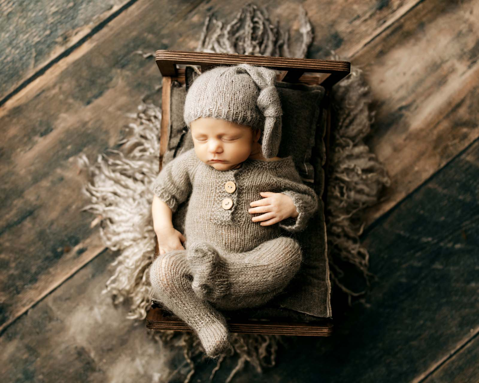 baby laying in tiny bed with sleeper hat on and matching romper