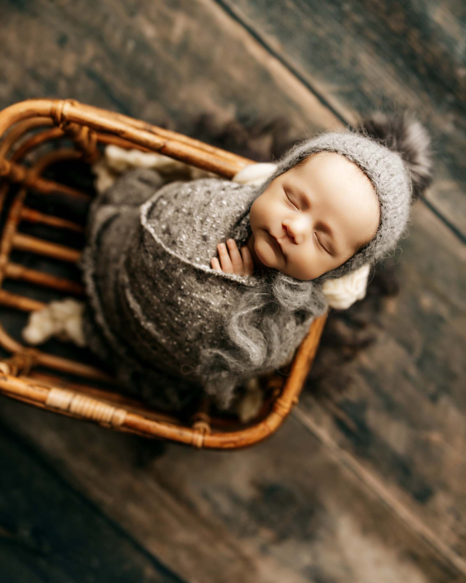 baby wrapped in dark gray inside basket with bonnet on
