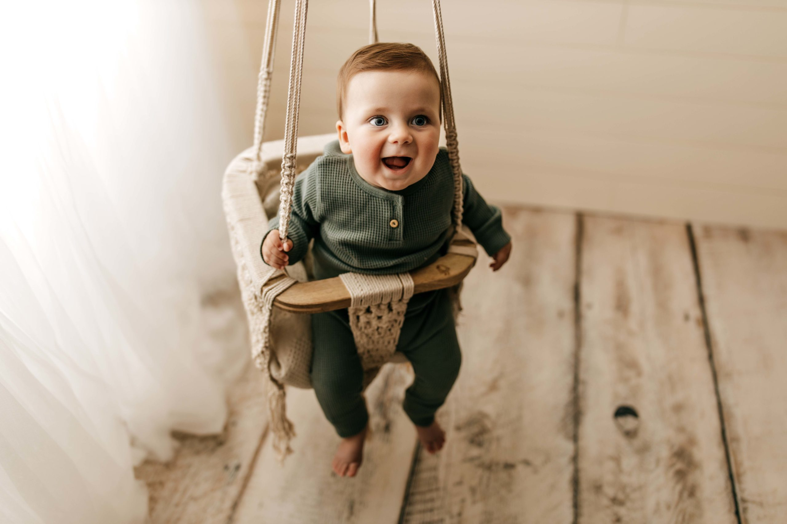 six month old in macrame swing smiling by window