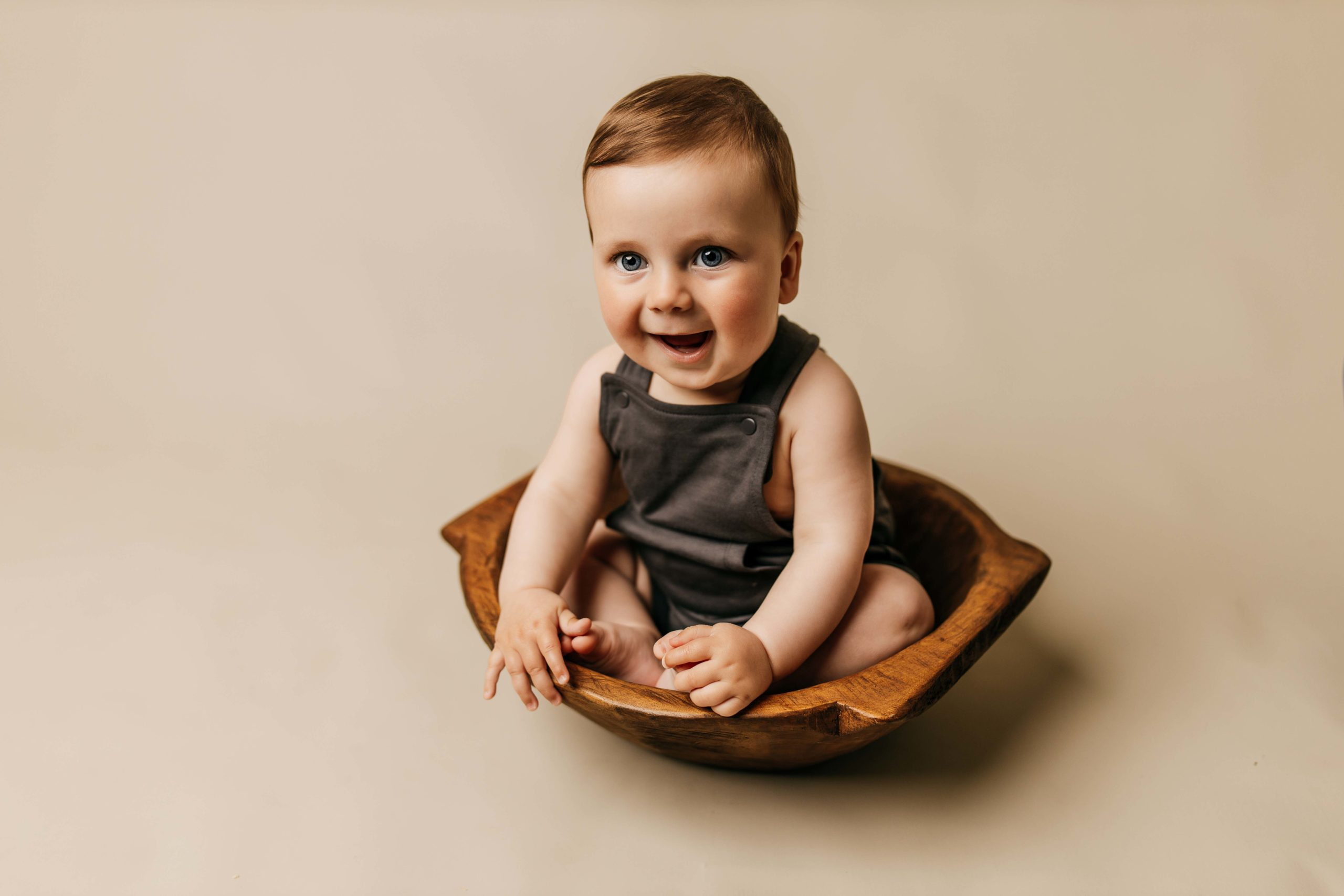 six month old sitting in dough bowl on tan backdrop