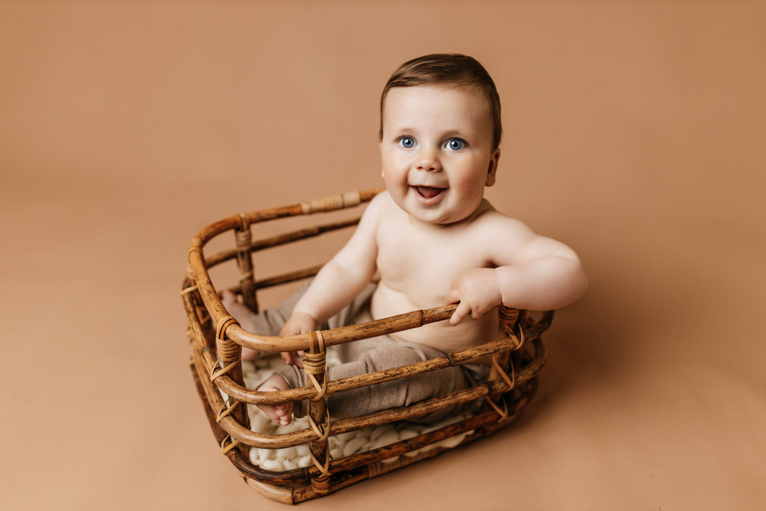 six month old sitting in bamboo basket on tan backdrop