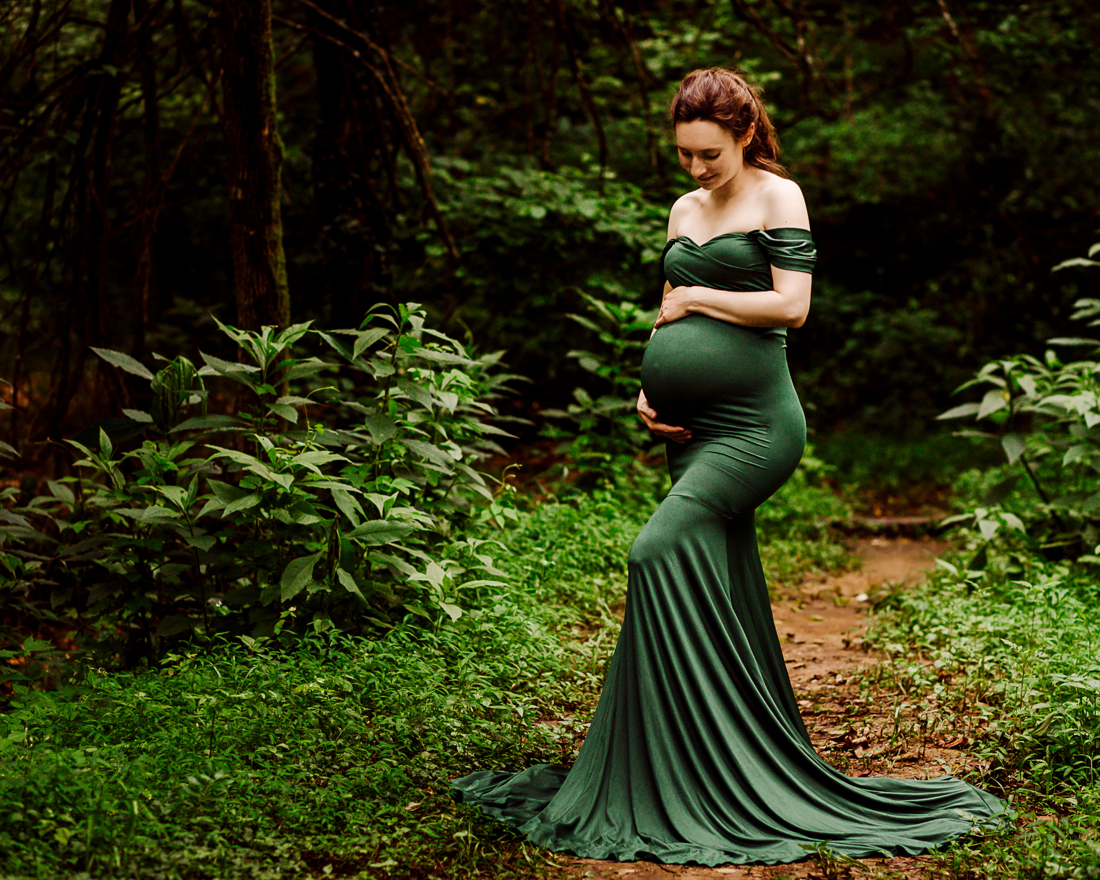 pregnant woman standing in wooded area while cradling her baby belly