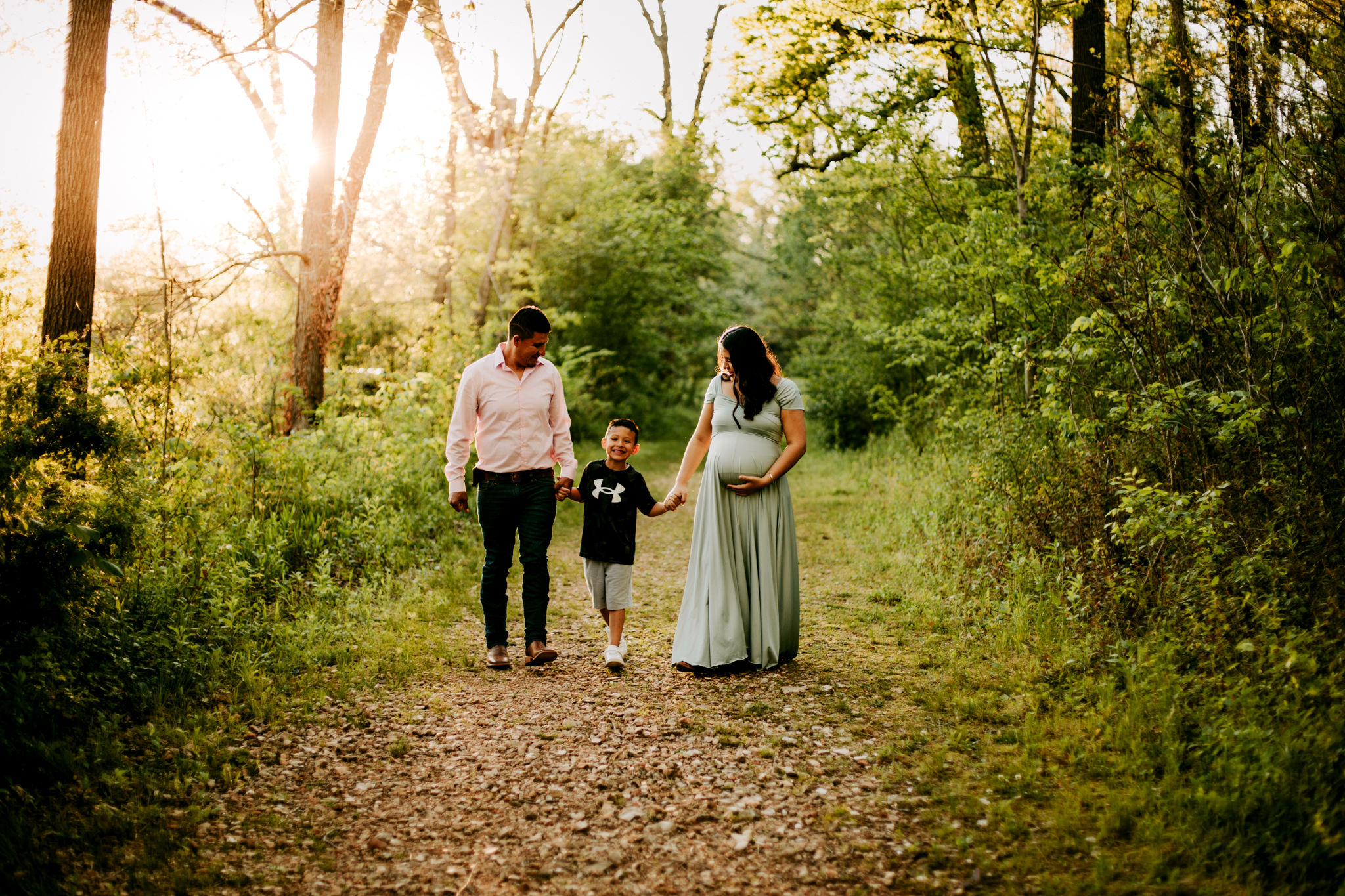 Family walking down dirt path while holding hands