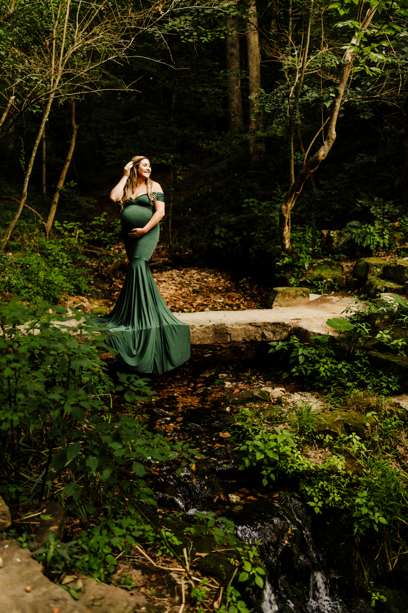 pregnant woman standing on stone bridge in wooded area in dark green dress