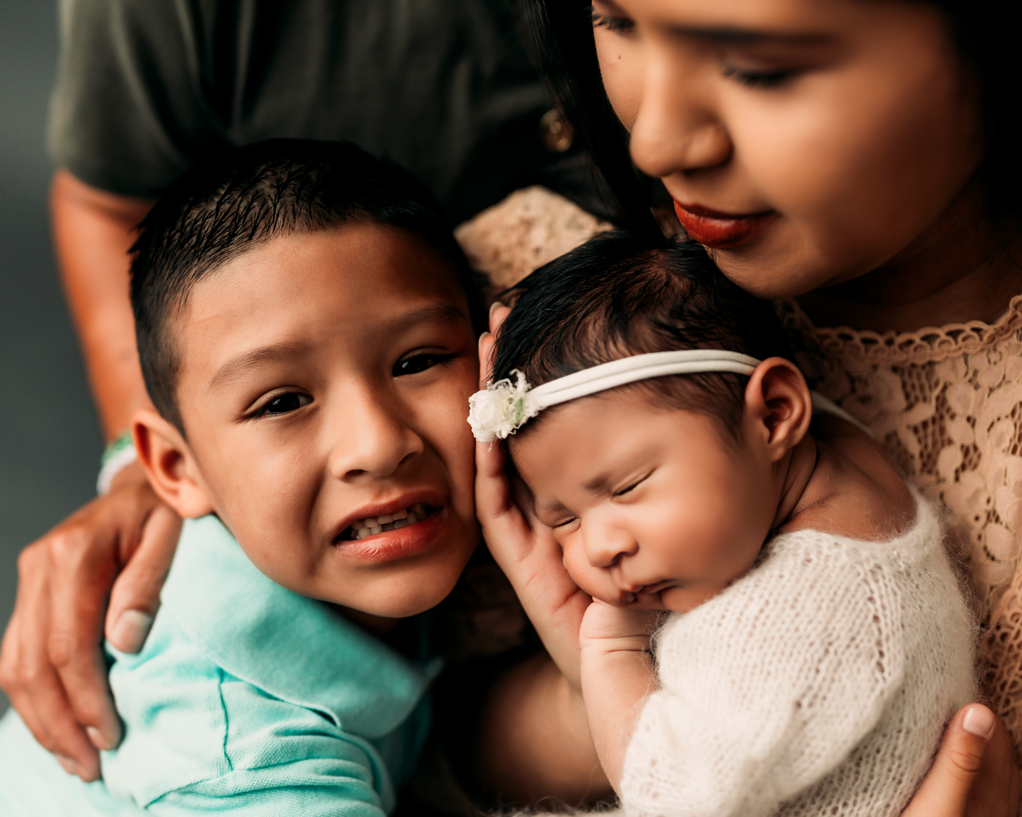 brother cuddling with baby sister in photography studio