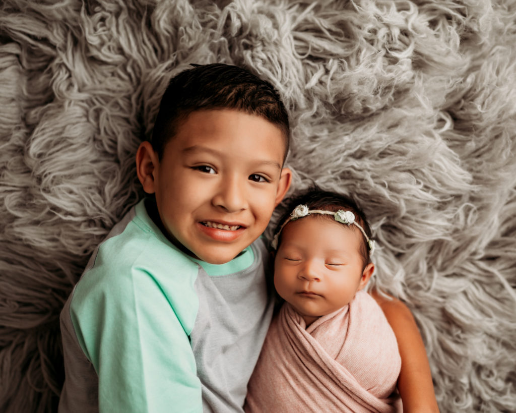 brother holding wrapped little sister on gray flokati rug during newborn photography session