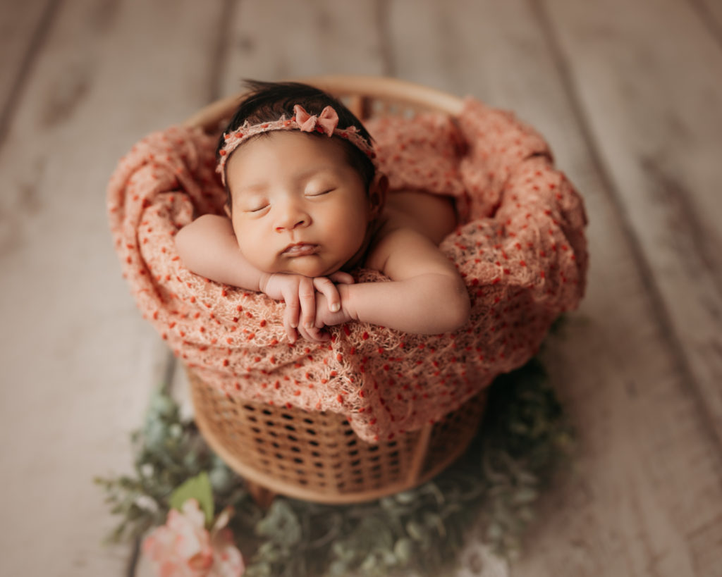 newborn on white wood floor posed in a bamboo basket during newborn photography session