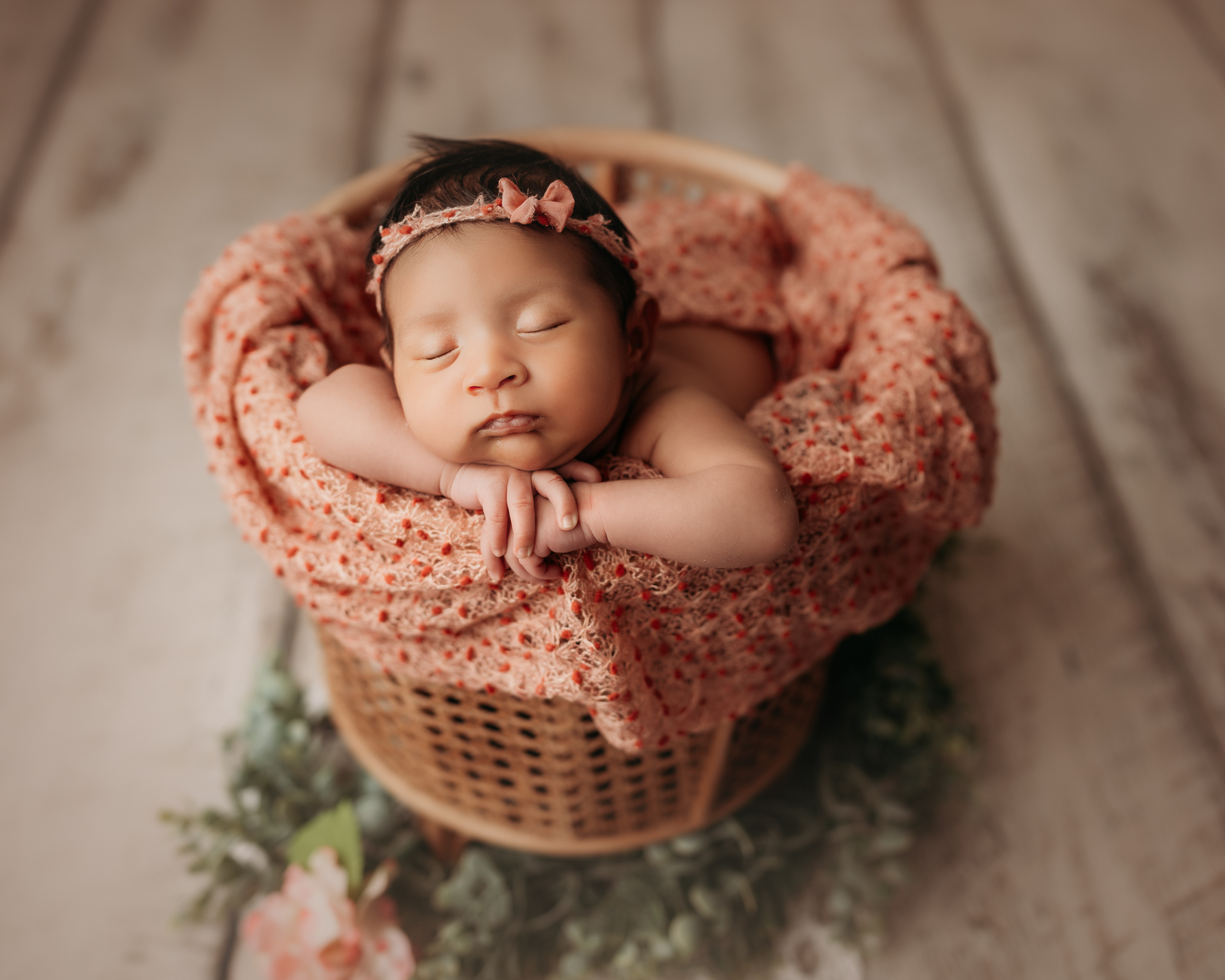 newborn on white wood floor posed in a bamboo basket