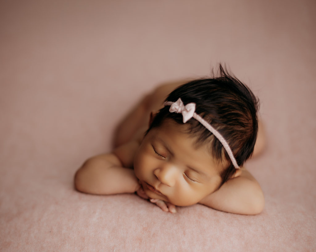 newborn on pink backdrop with head resting on hands during newborn photography session