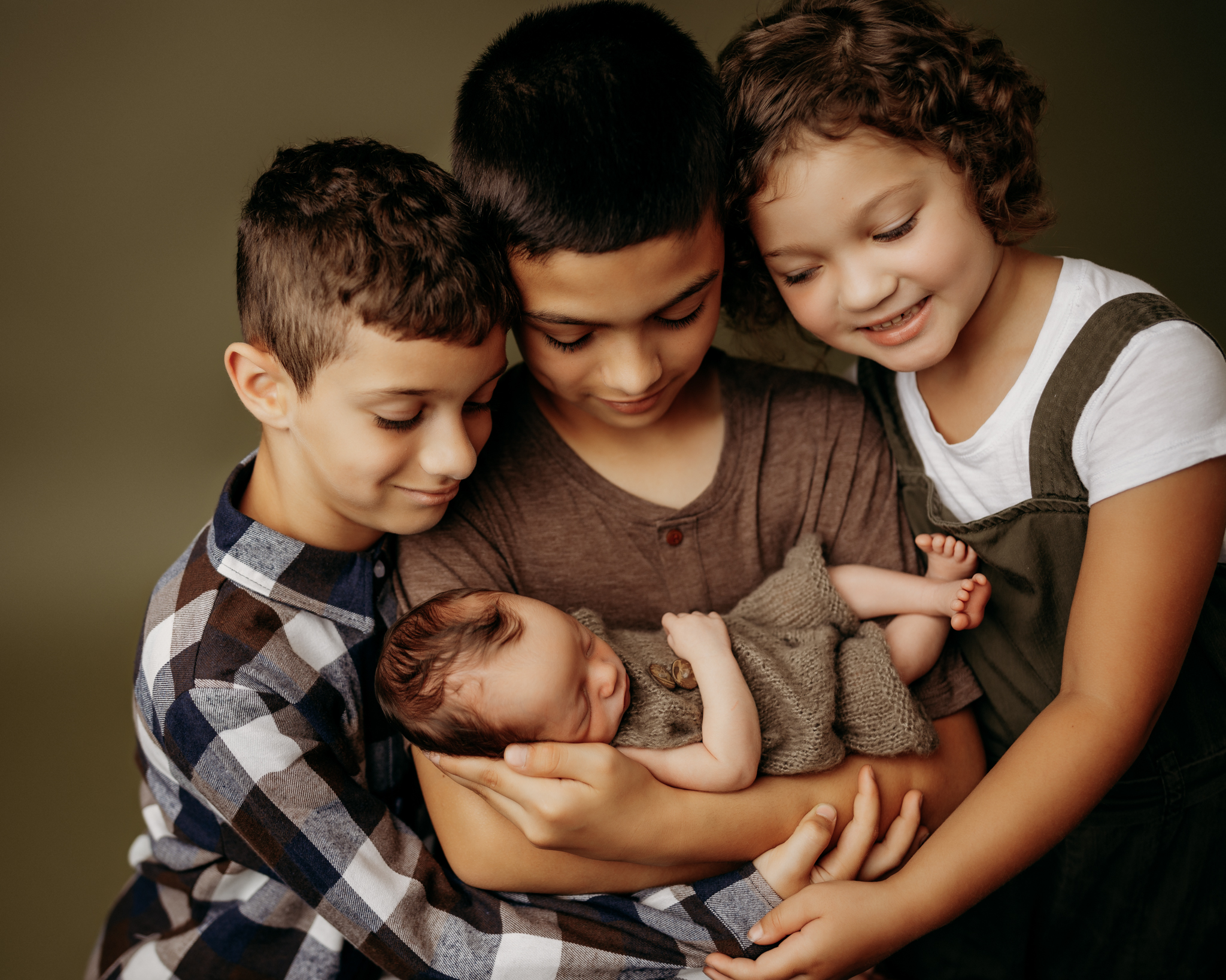 siblings holding baby brother on dark green backdrop while looking at their sibling
