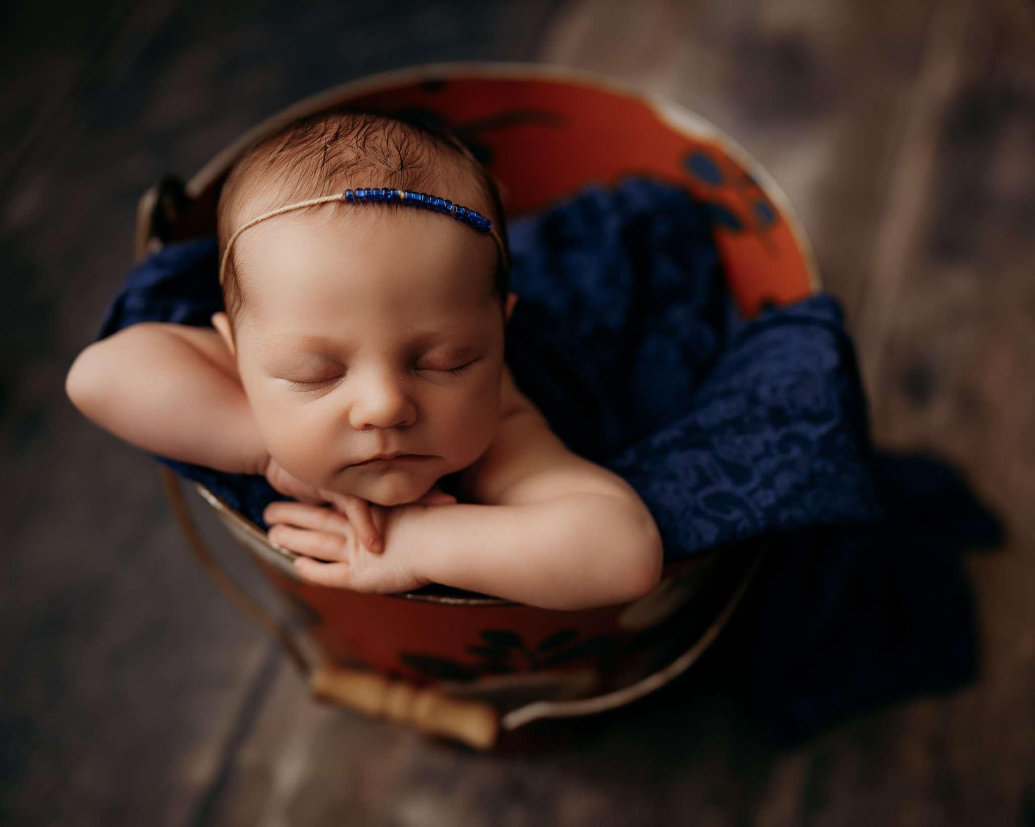baby in bucket pose on dark wood floor with bucket being orange and navy floral