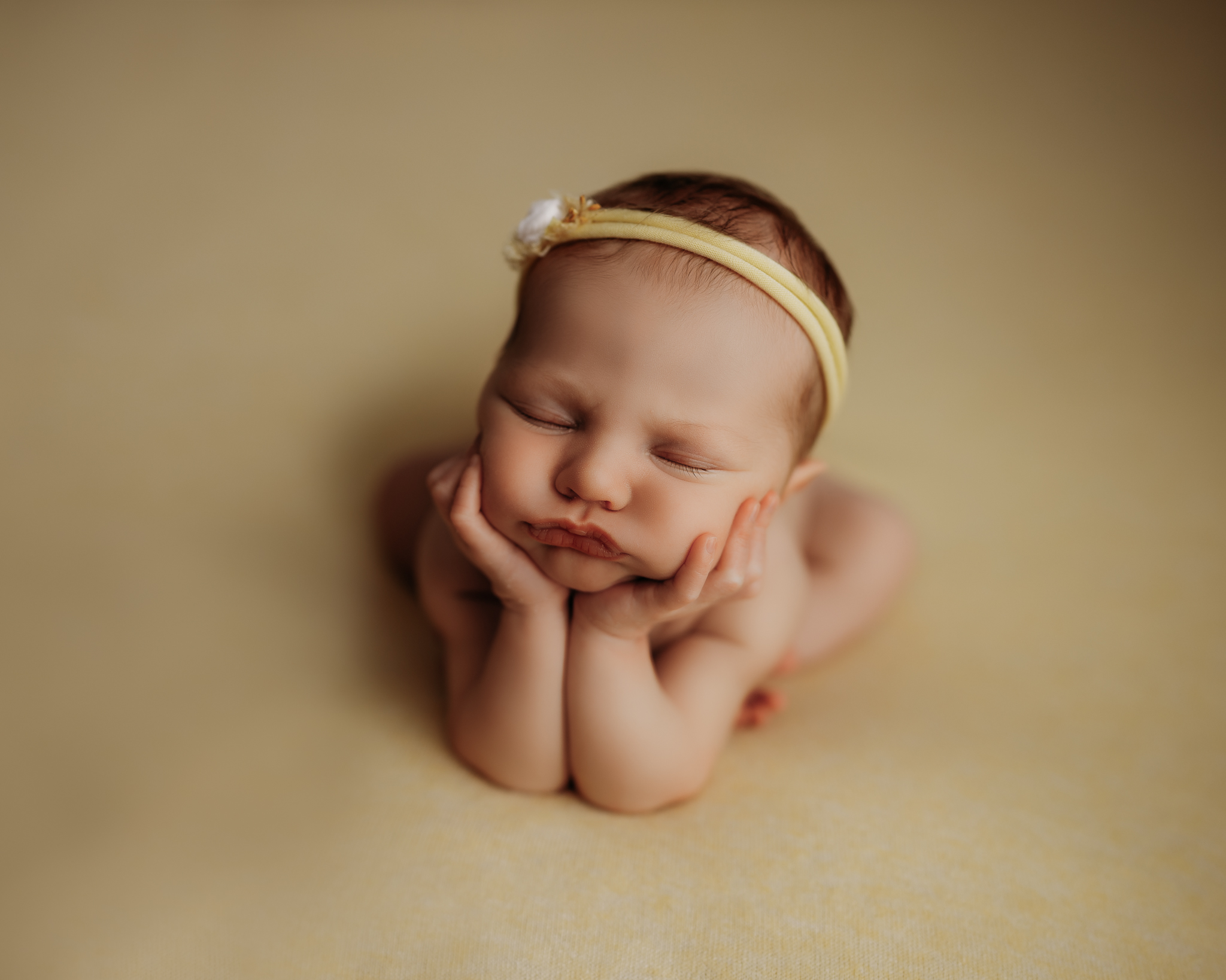newborn in frog pose on yellow backdrop