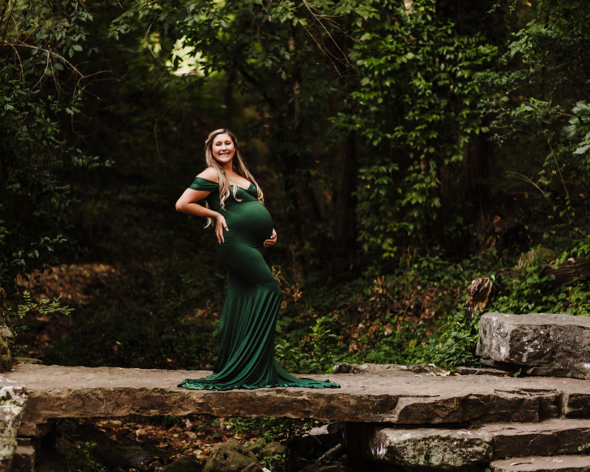 maternity photography session at Crystal Bridges along the art trail on rock ledge. Mom is holding belly and smiling at camera surrounded by foliage