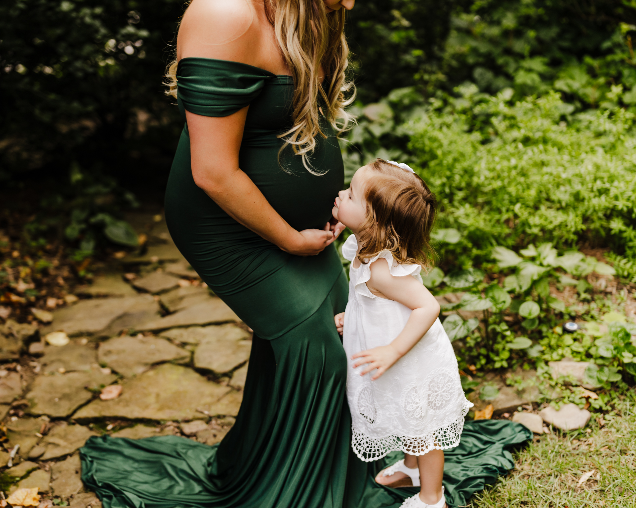 pregnant woman in green dress leaning over for her daughter to kiss her belly in wooded area