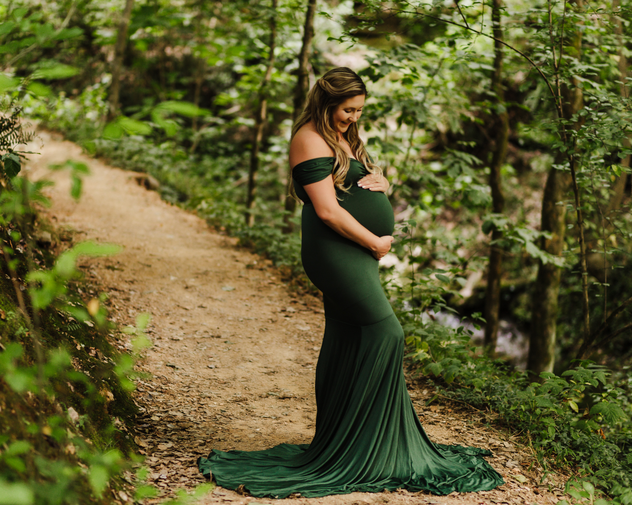 pregnant mom standing on trail surrounded by foliage while looking down and cradling her baby belly.