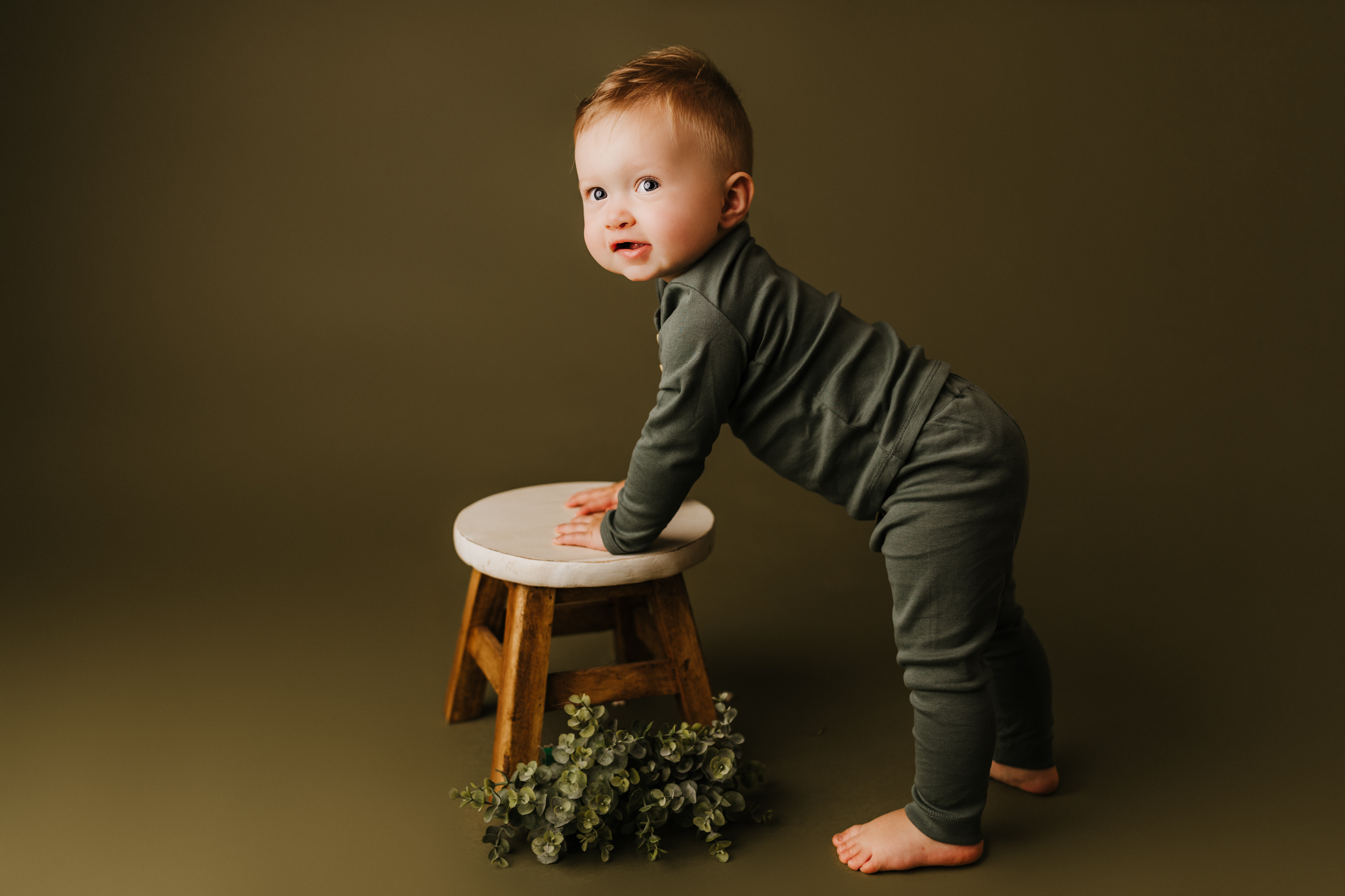 one year old leaning on stool while in front of green backdrop wearing green clothes and smiling at camera