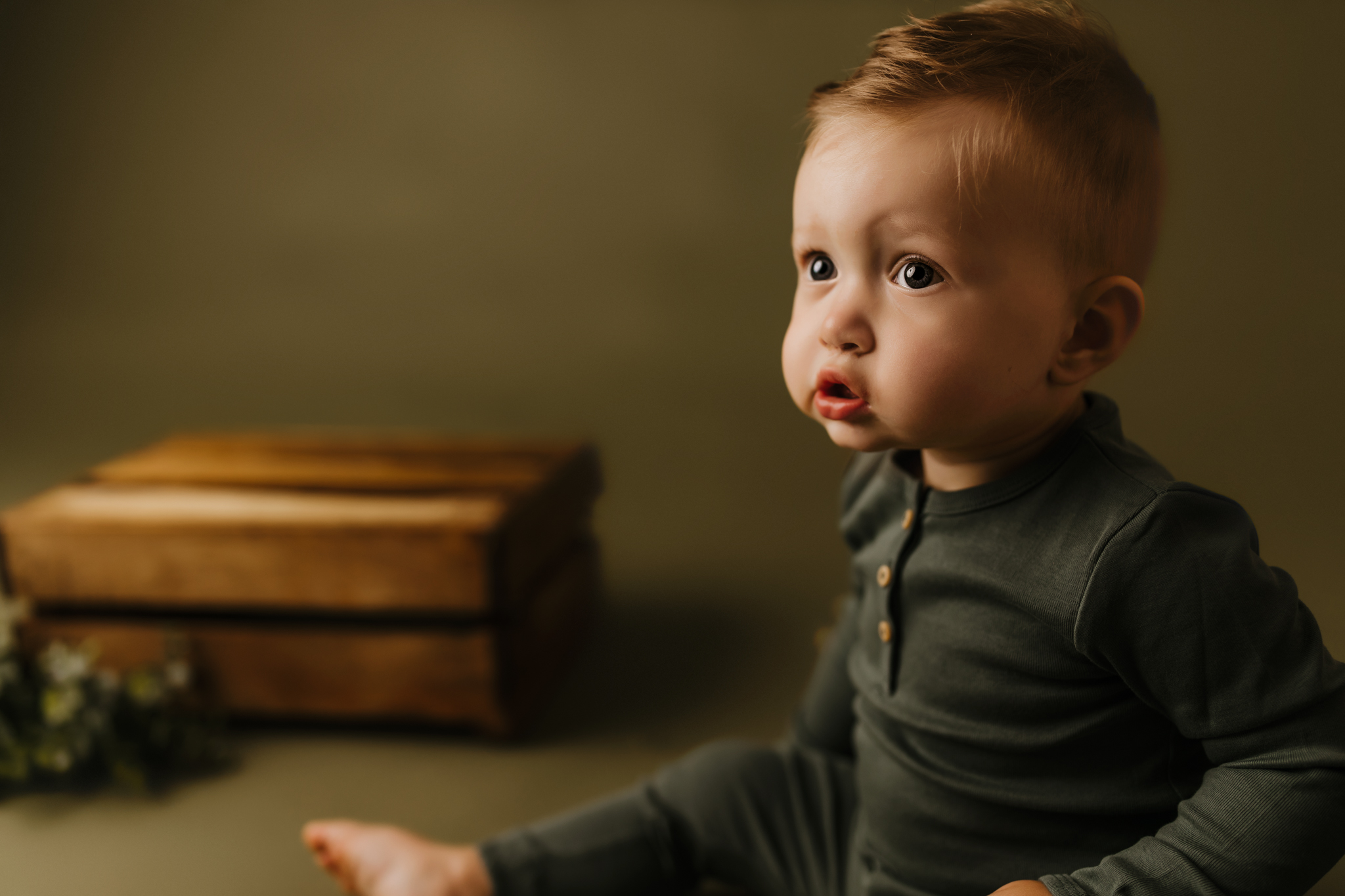one year old sitting on olive green backdrop while staring at the movie playing in the studio
