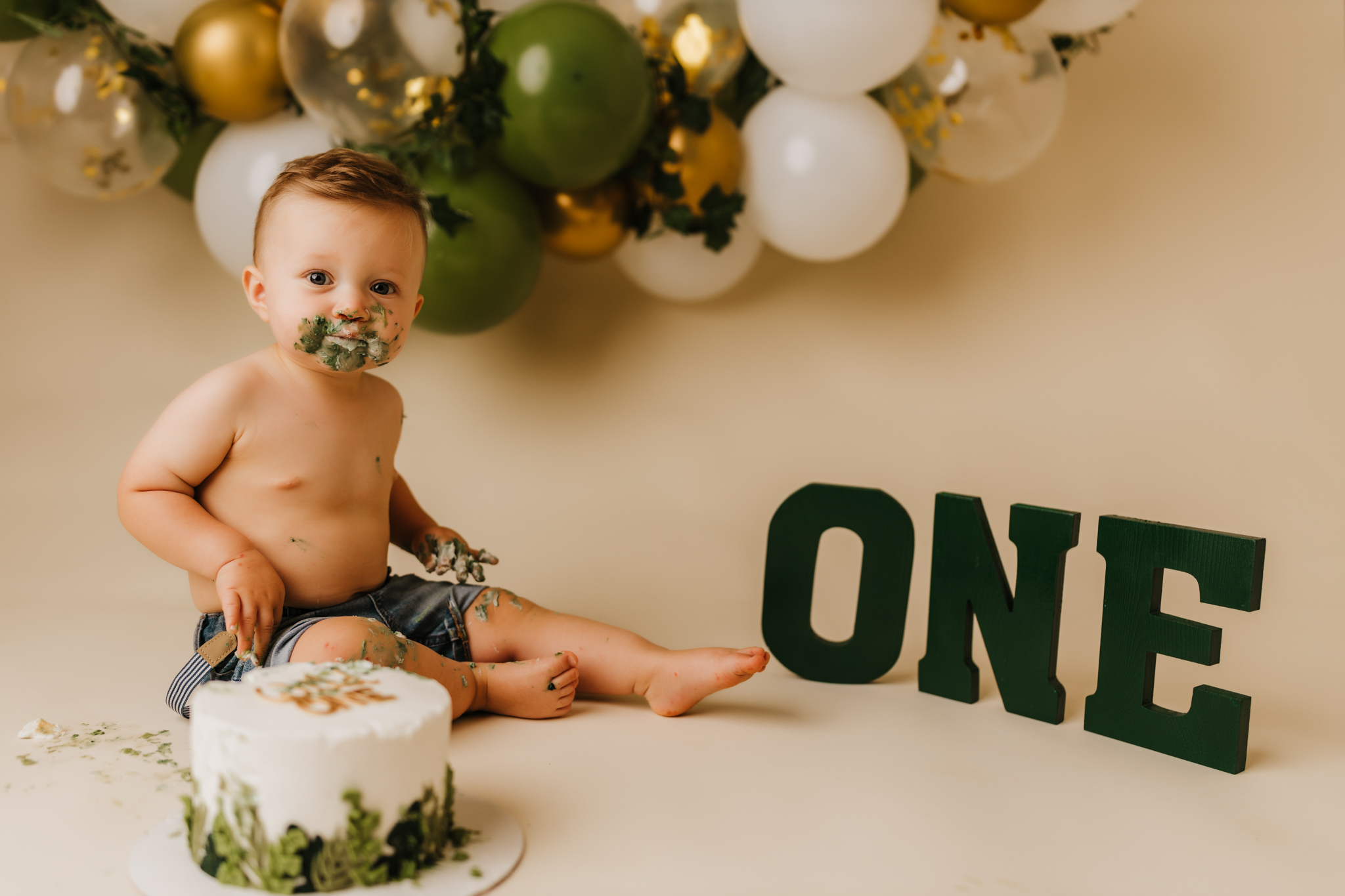 one year old enjoying his cake in studio on a cream backdrop in front of green, gold, and white balloon garland