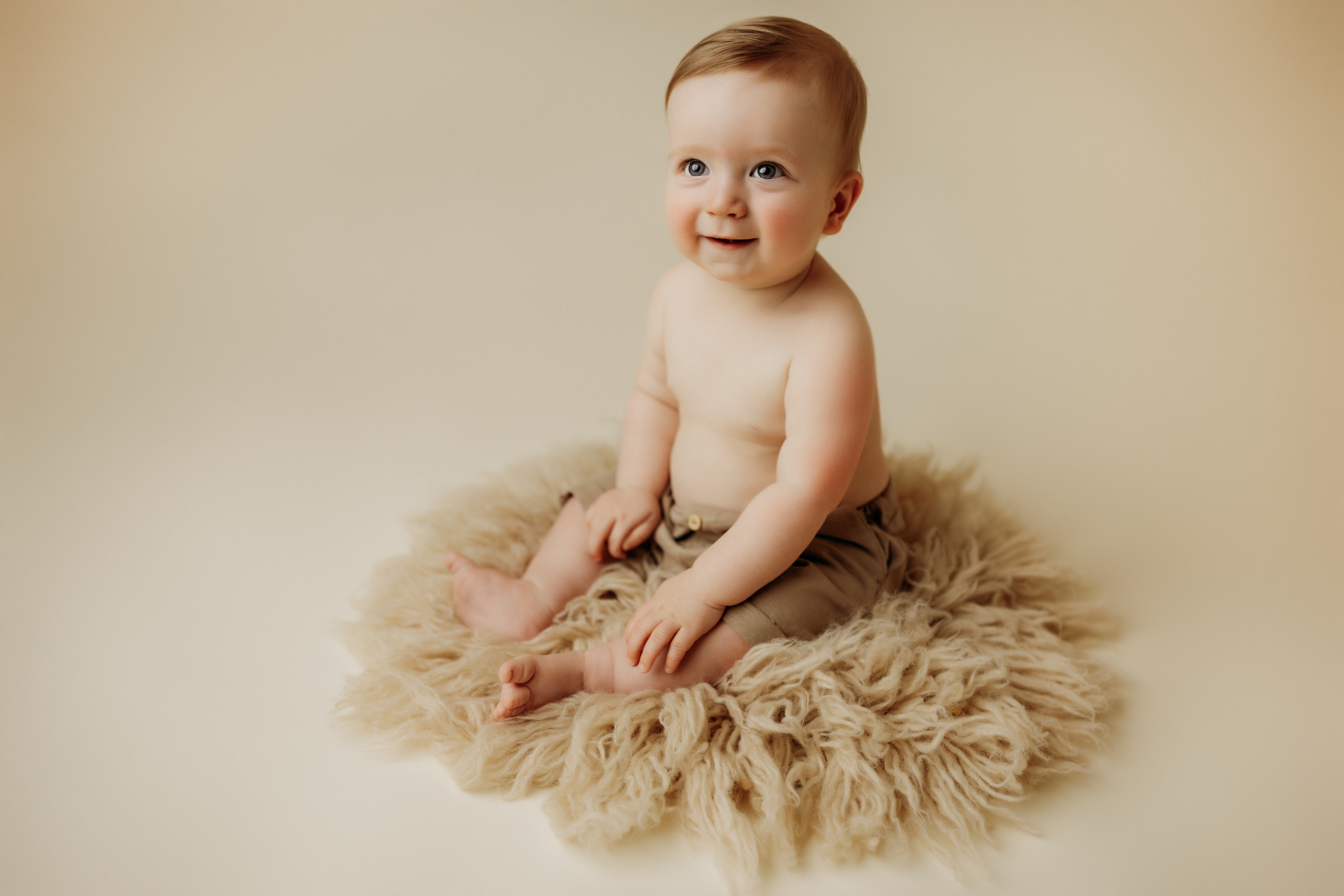 nwa childrens session with baby boy on tan flokati round rug and shorts while smiling
