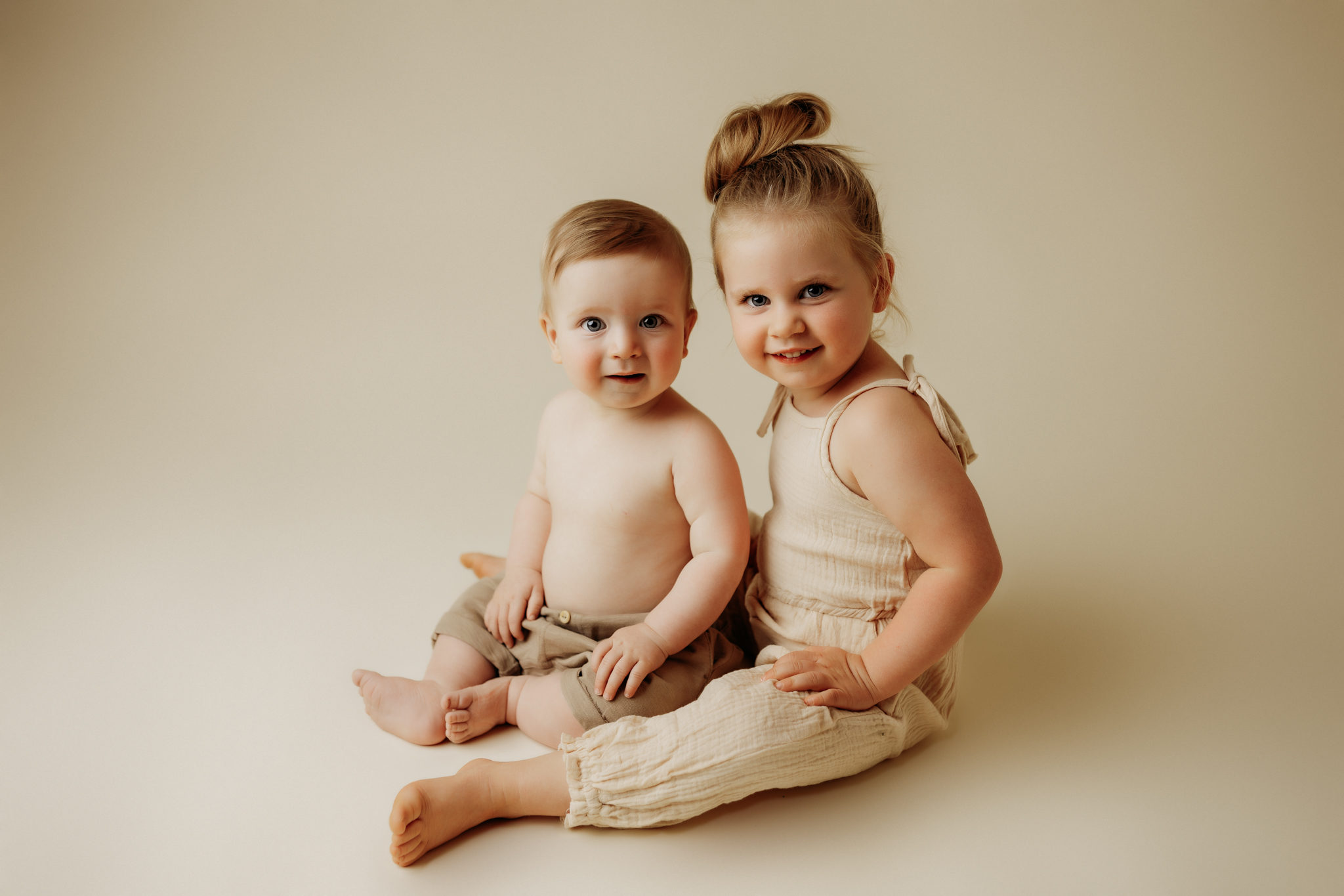 siblings posed next to eachother smiling at camera on cream backdrop