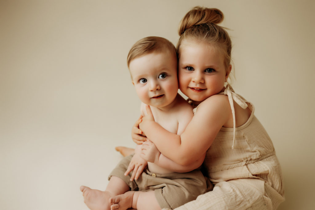 Brother and sister hugging on cream colored backdrop while smiling at camera