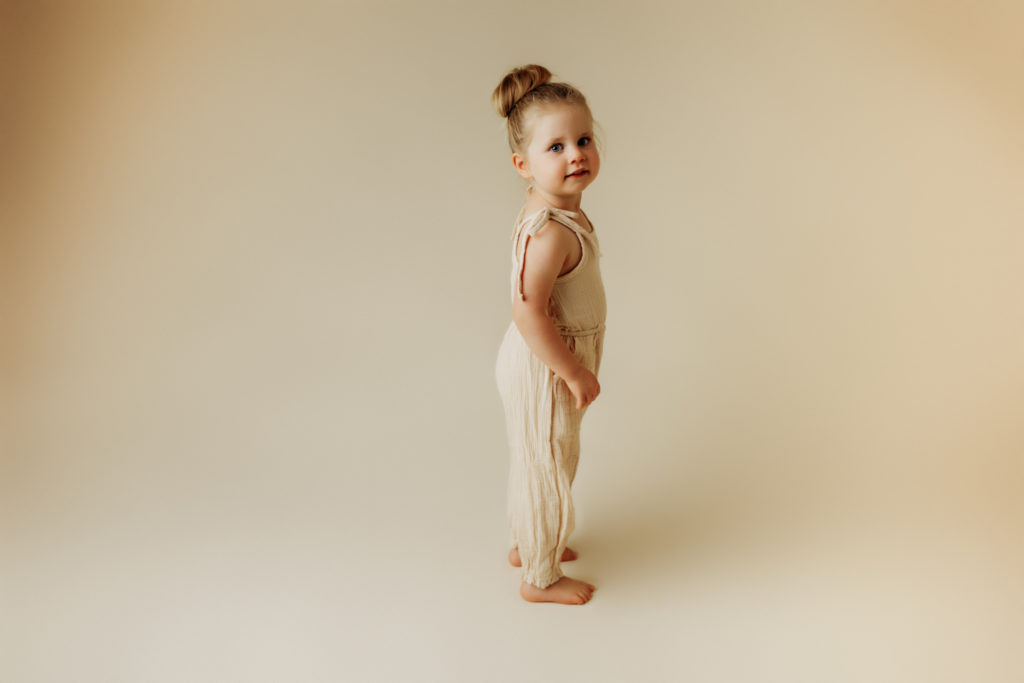 Toddler standing on cream colored backdrop with matching romper looking at camera