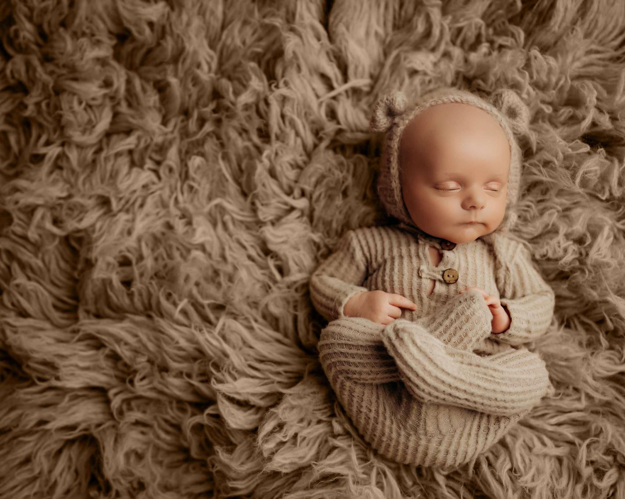 baby on light brown flokati rug with feet up and bear bonnet sleeping
