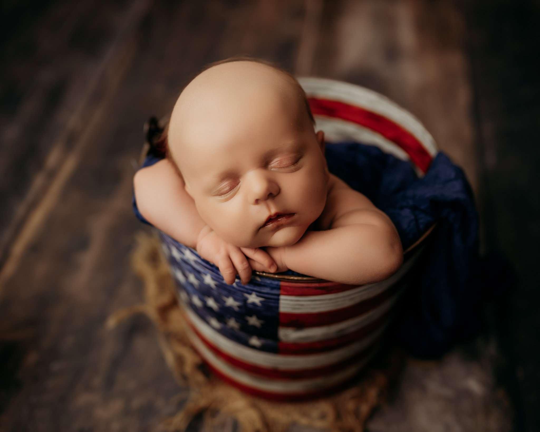 baby in bucket sleeping with head on its hands