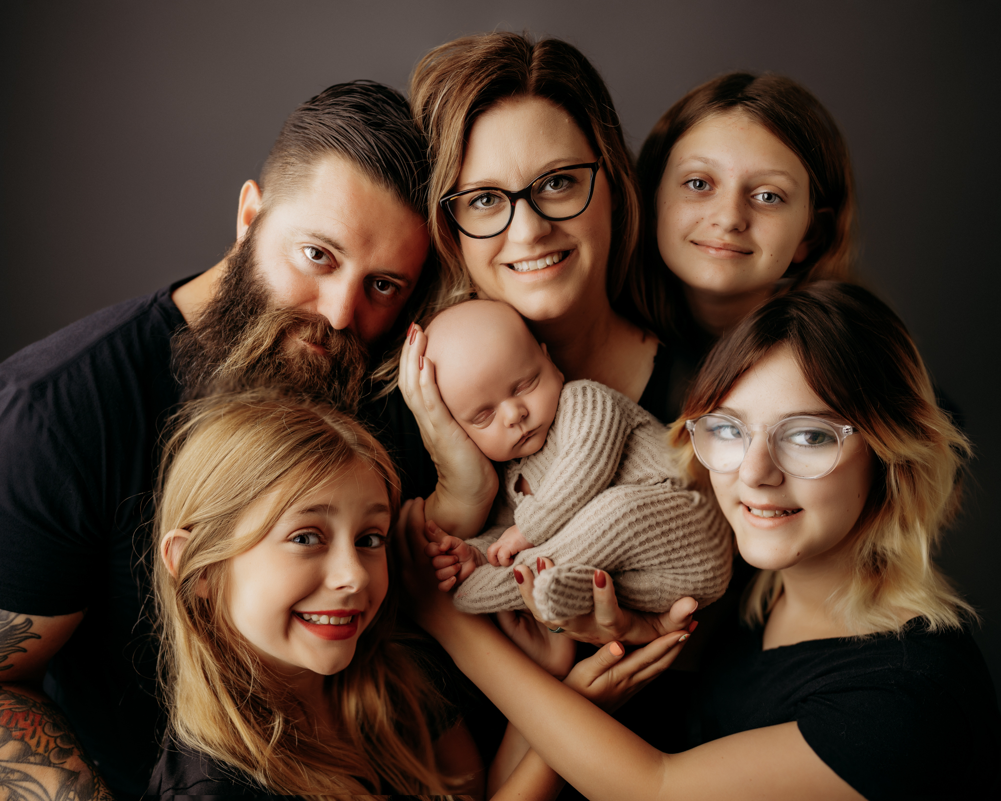 family image on dark gray backdrop surrounding the newborn in the family
