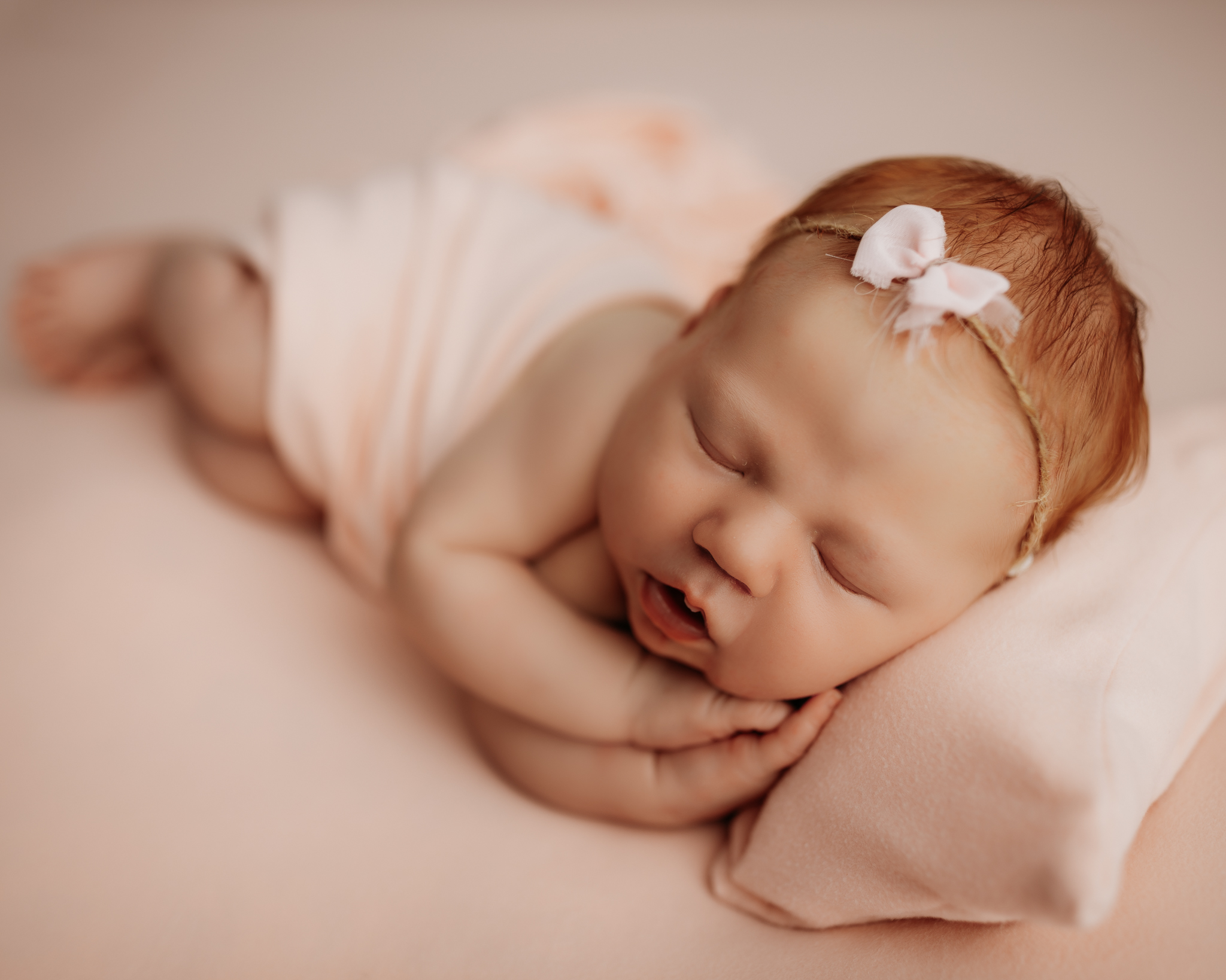 NWA newborn photography session on pink backdrop with baby in side laying pose with pillow under her head