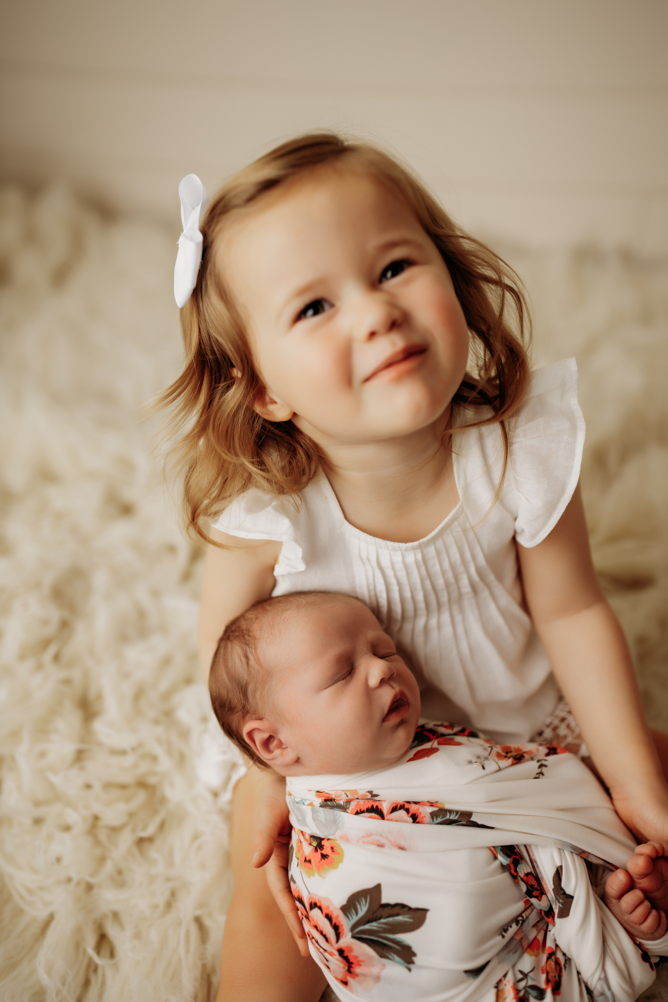 nwa newborn wrapped in a white and floral wrap sleeping while in big sisters arms while big sister looks and smiles at the camera