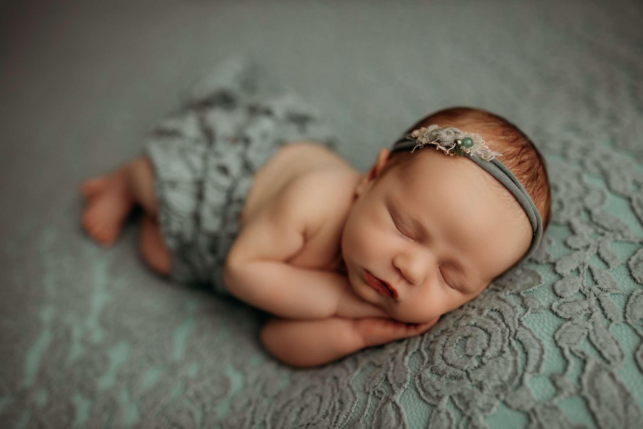 nwa newborn sleeping in side laying pose while facing camera sleeping