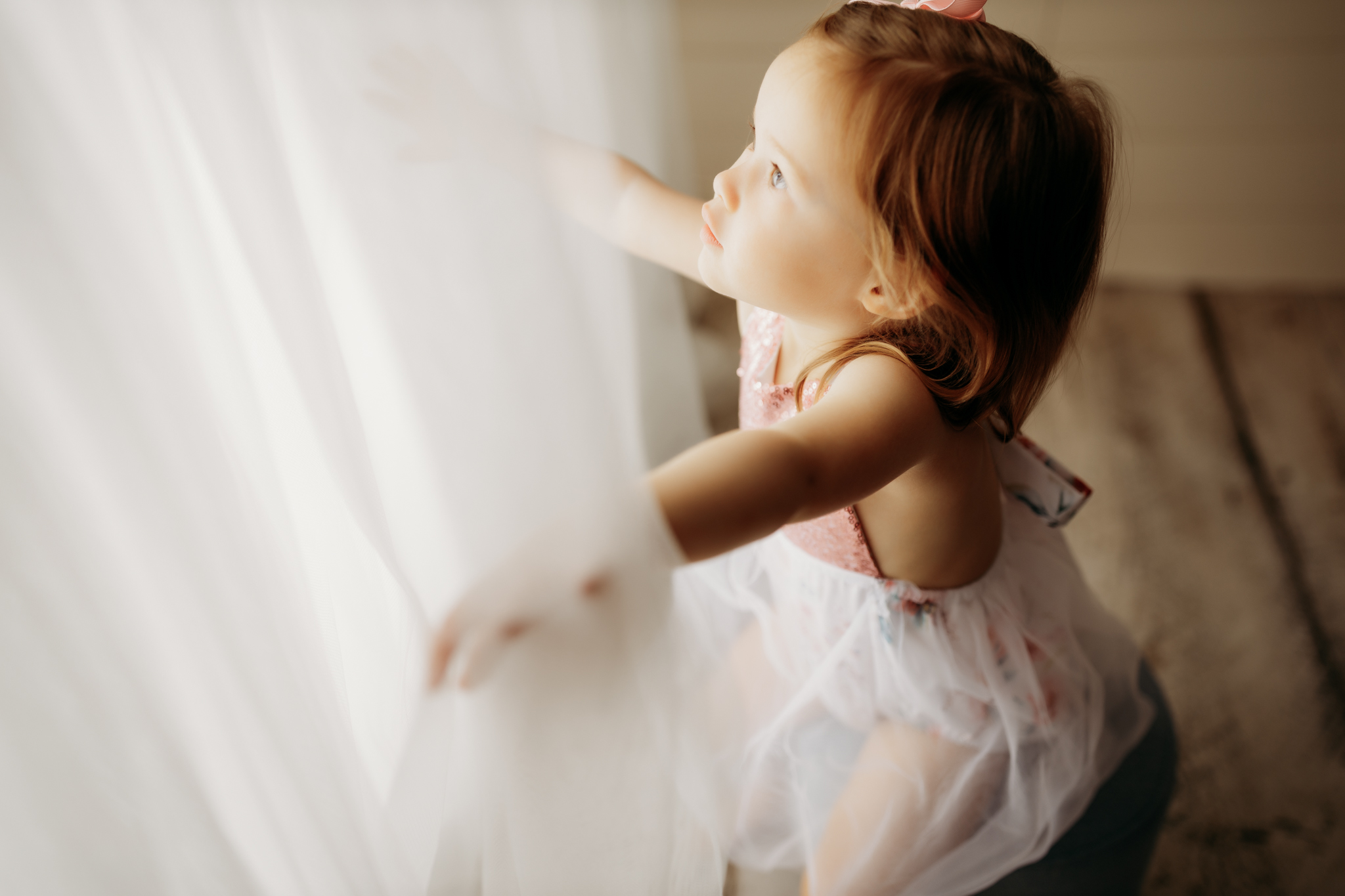 nwa childrens photography with child looking through faux window in studio