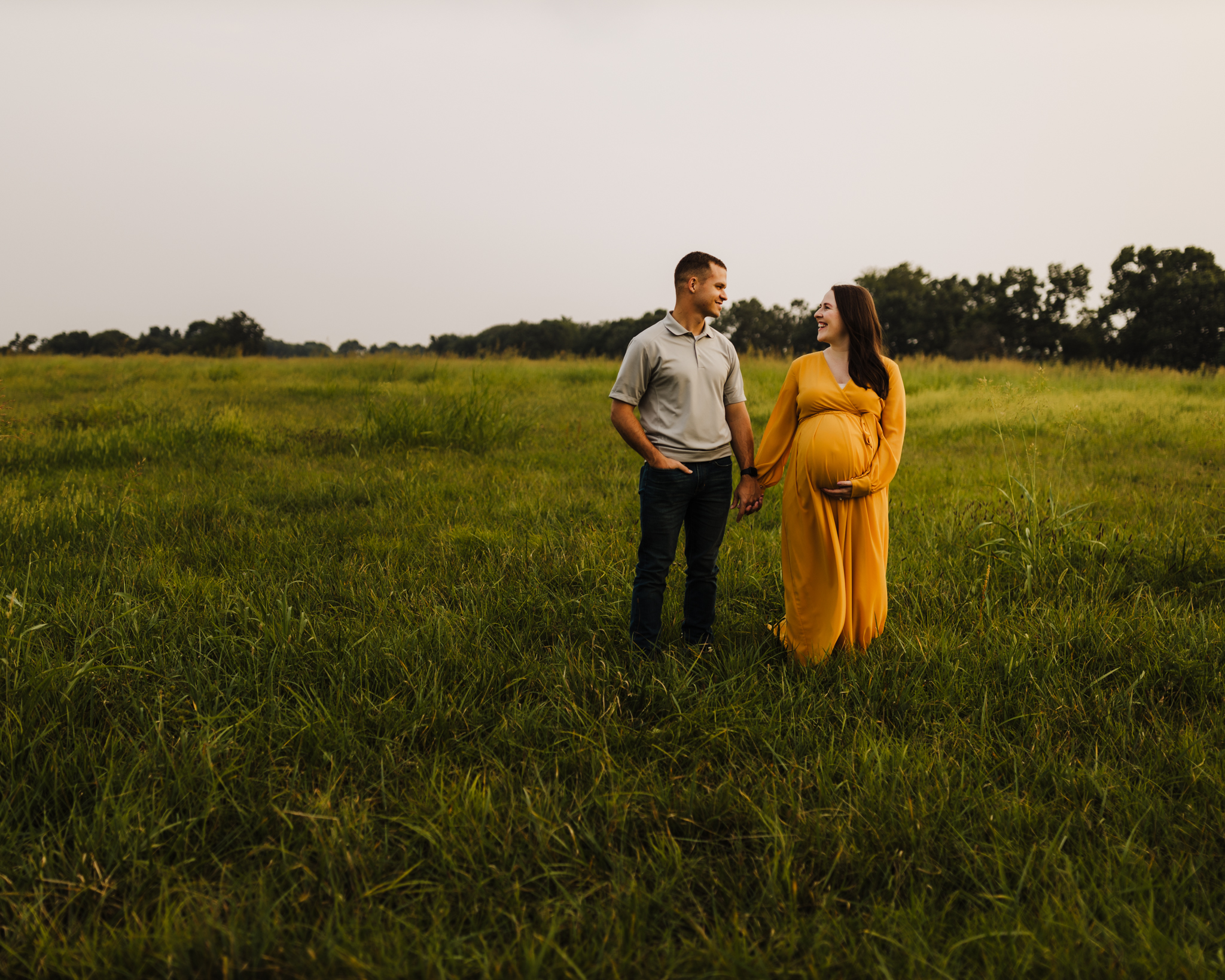 maternity images done in open field with mom wearing a yellow/orange dress