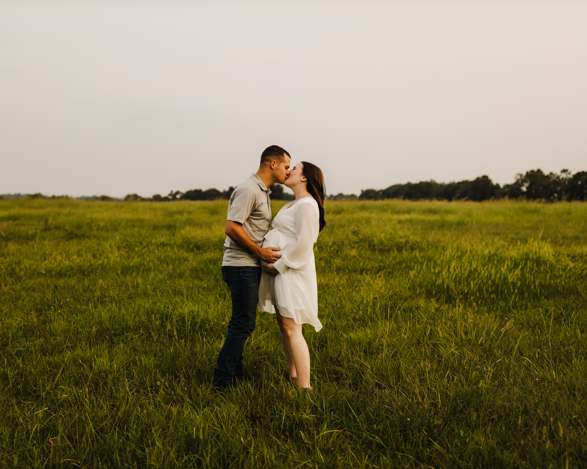 maternity photography session with mom kissing dad and mom in a white dress in an open field