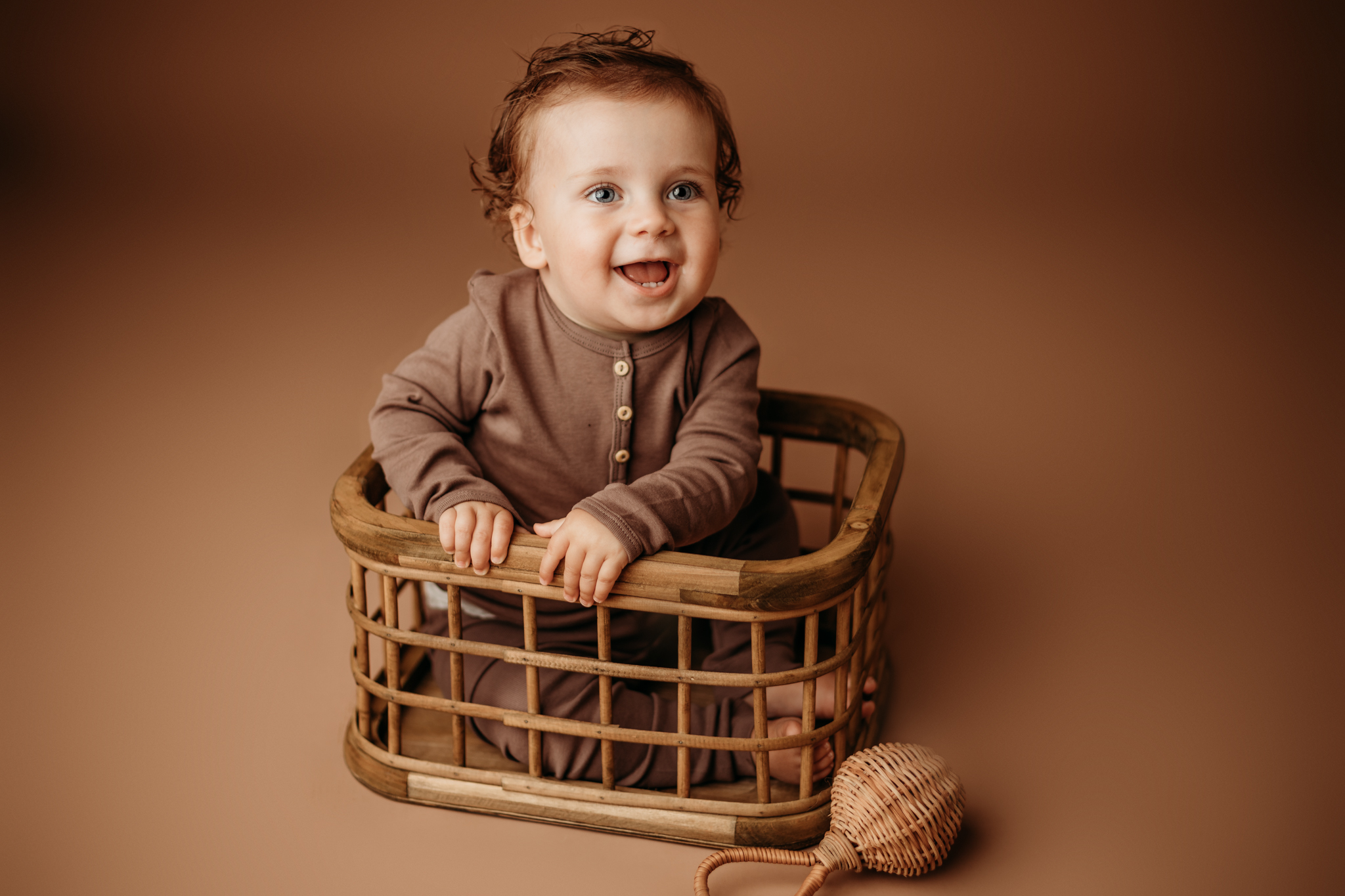 NWA one year little boy in studio on brown backdrop in crate smiling at the camera
